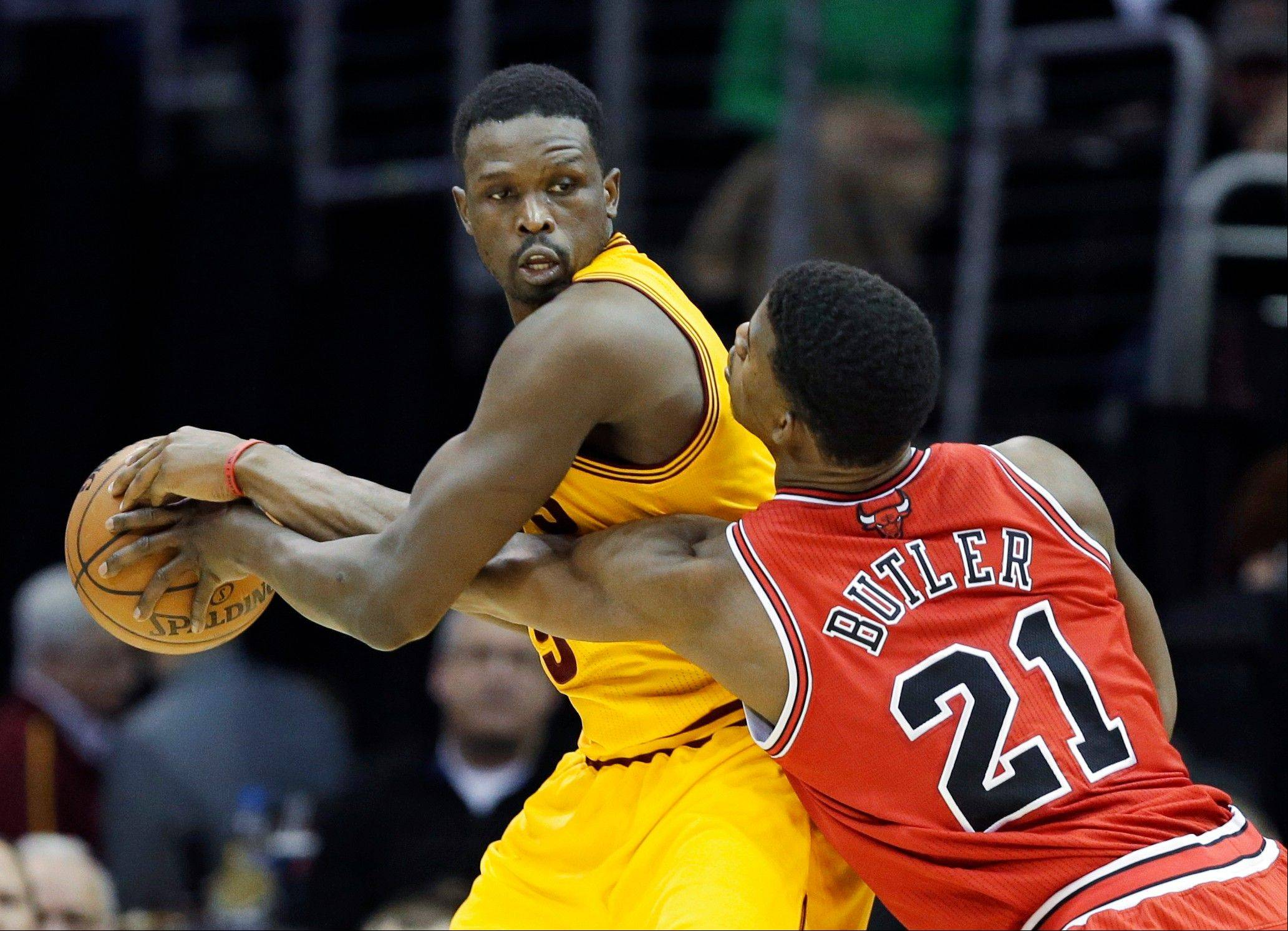 The Bulls' Jimmy Butler (21) tries to poke the ball away from Cleveland Cavaliers' Luol Deng during Wednesday night's game in Cleveland. The Bulls won 98-87.