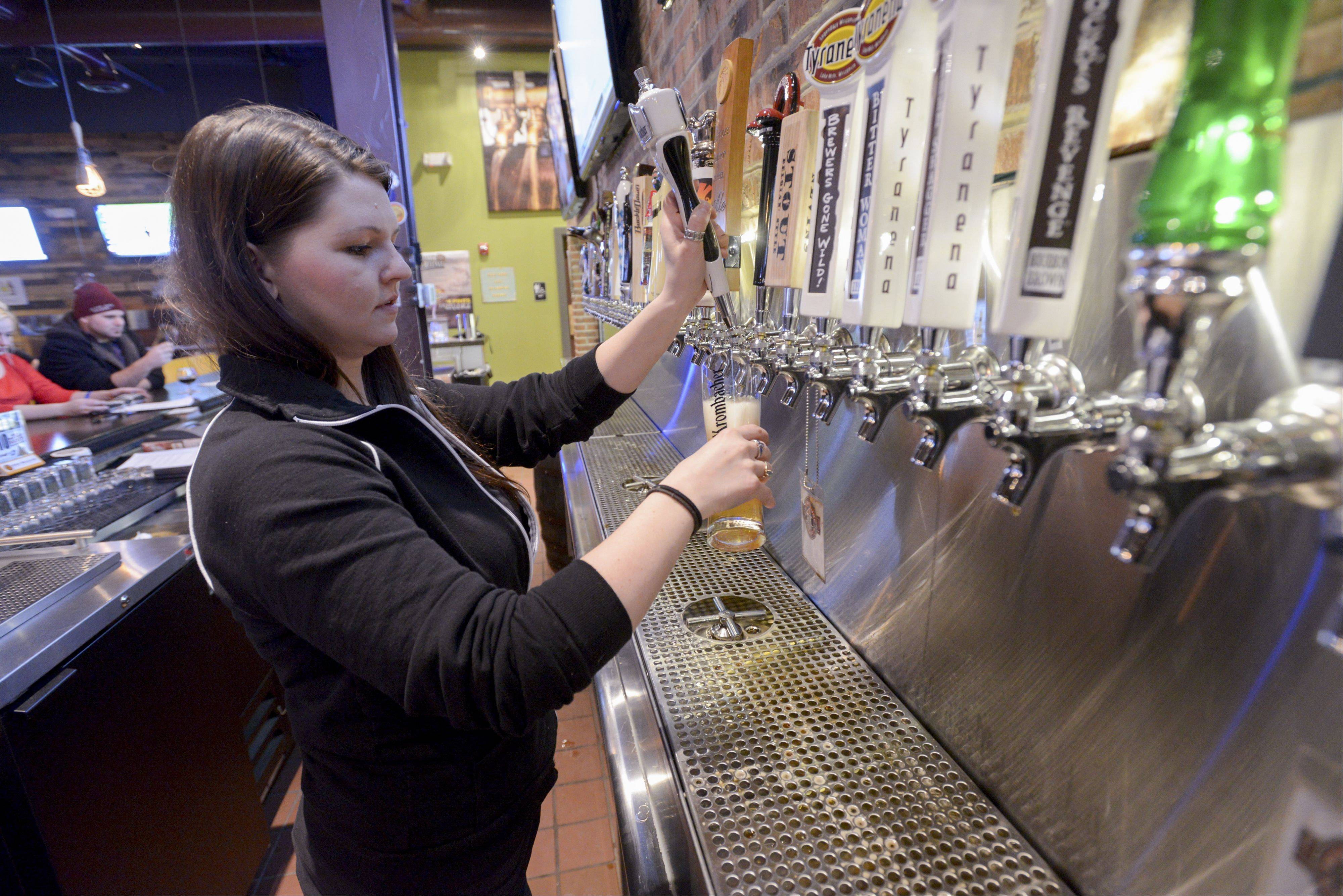 Paig Ginther pours a Krombacher Pilsner at the Beer House in Lombard's Yorktown Shopping Center.