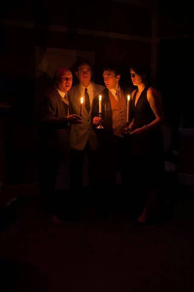 "Lars Timpa as William Blore, from left, Geoffrey Maher as Dr. Armstrong, Sean Ogren as Philip Lombard and Sharon Vos as Vera Claythorne examine their mysterious situation by candlelight in Wheaton Drama's production of Agatha Christie's ""And Then There Were None."""