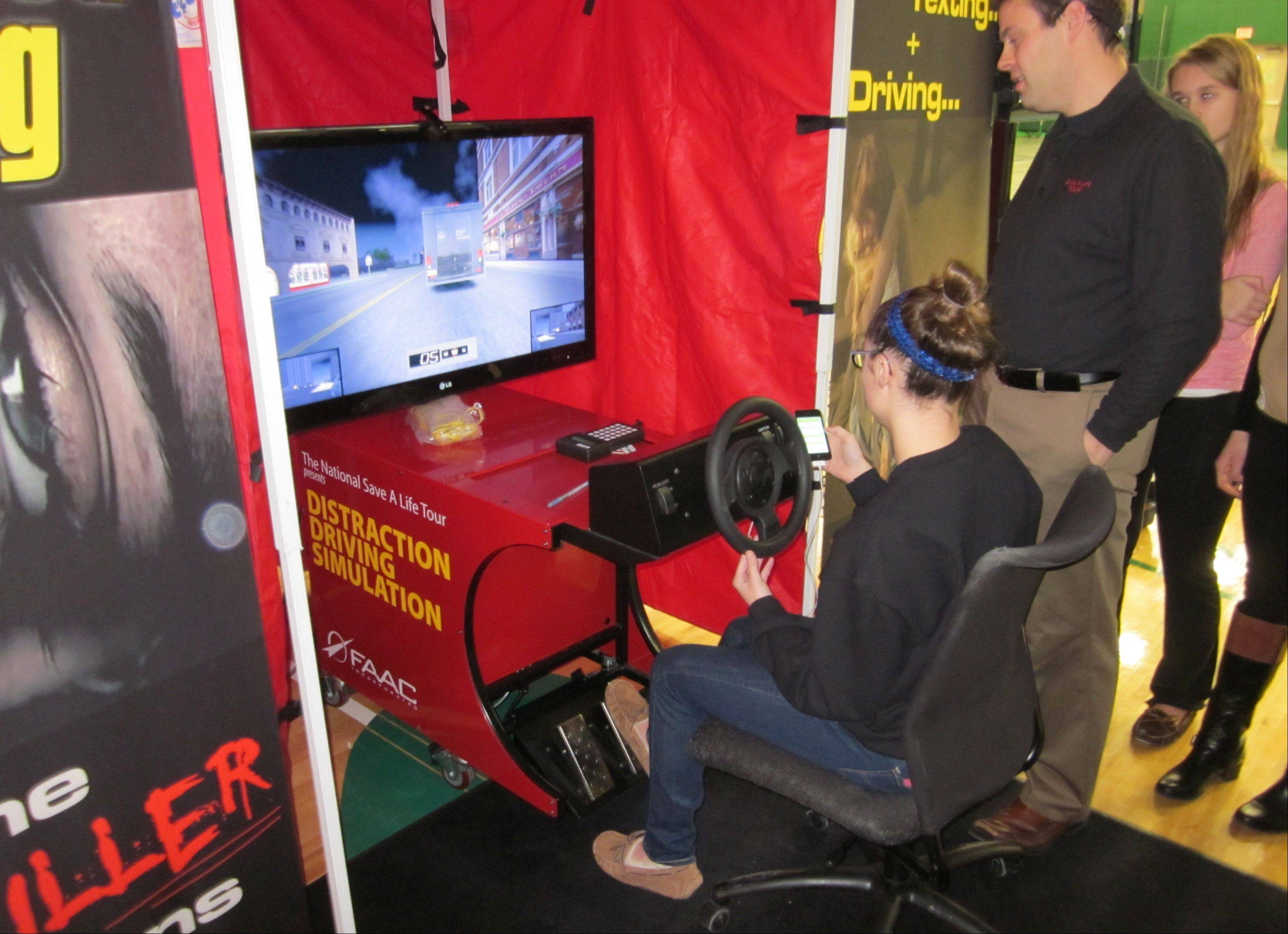 "Grayslake Central High School junior Emma Eiserman, under supervision by Jonathan Saigeon, learns some lessons on a distracted driver simulator there Wednesday as part of a ""Save a Life Tour"" sponsored by Northwestern Lake Forest Hospital."