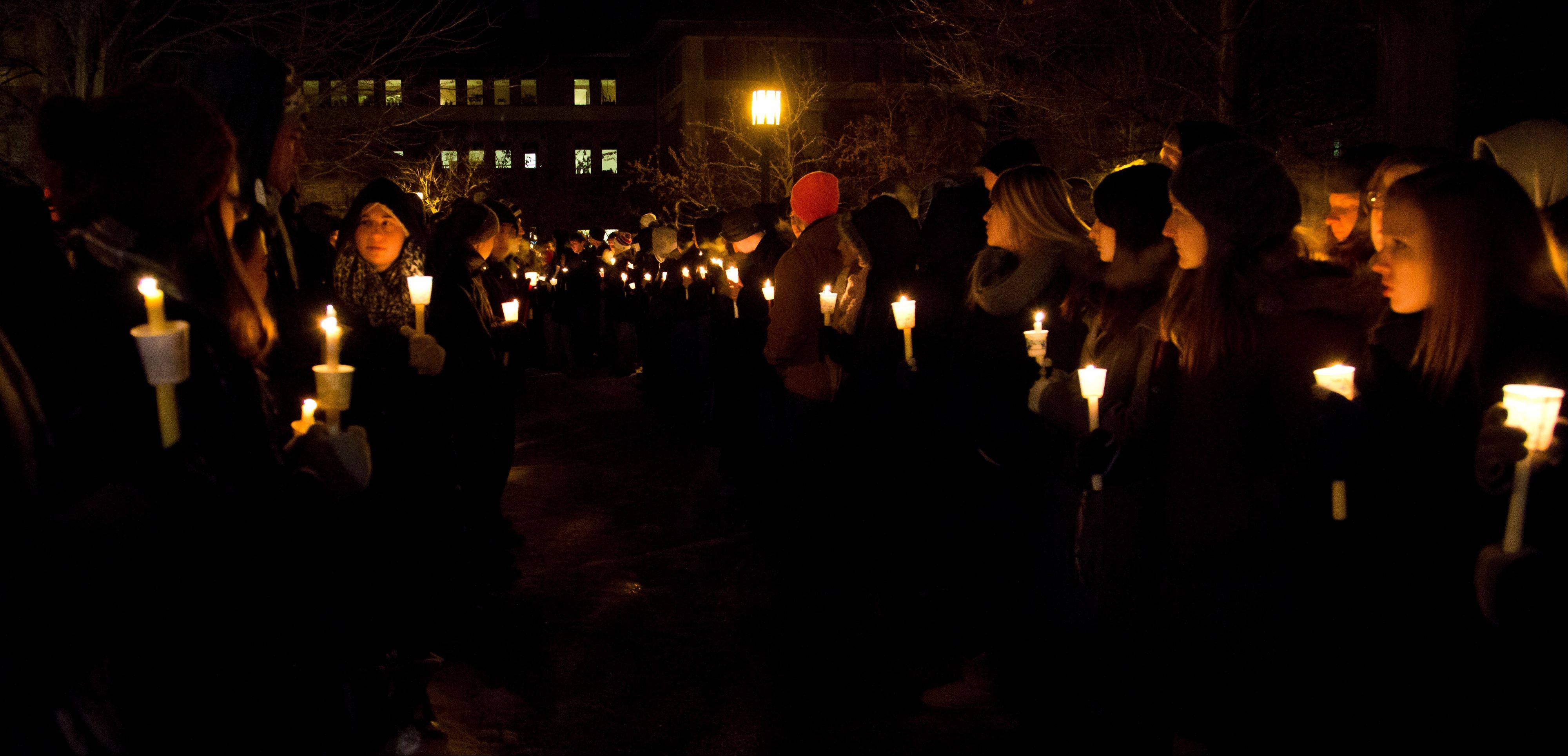 A path is lit for members of the Purdue marching band during a vigil for a teaching assistant who was fatally shot on campus at Purdue University, on Tuesday, Jan. 21, 2014, in West Lafayette, Ind.