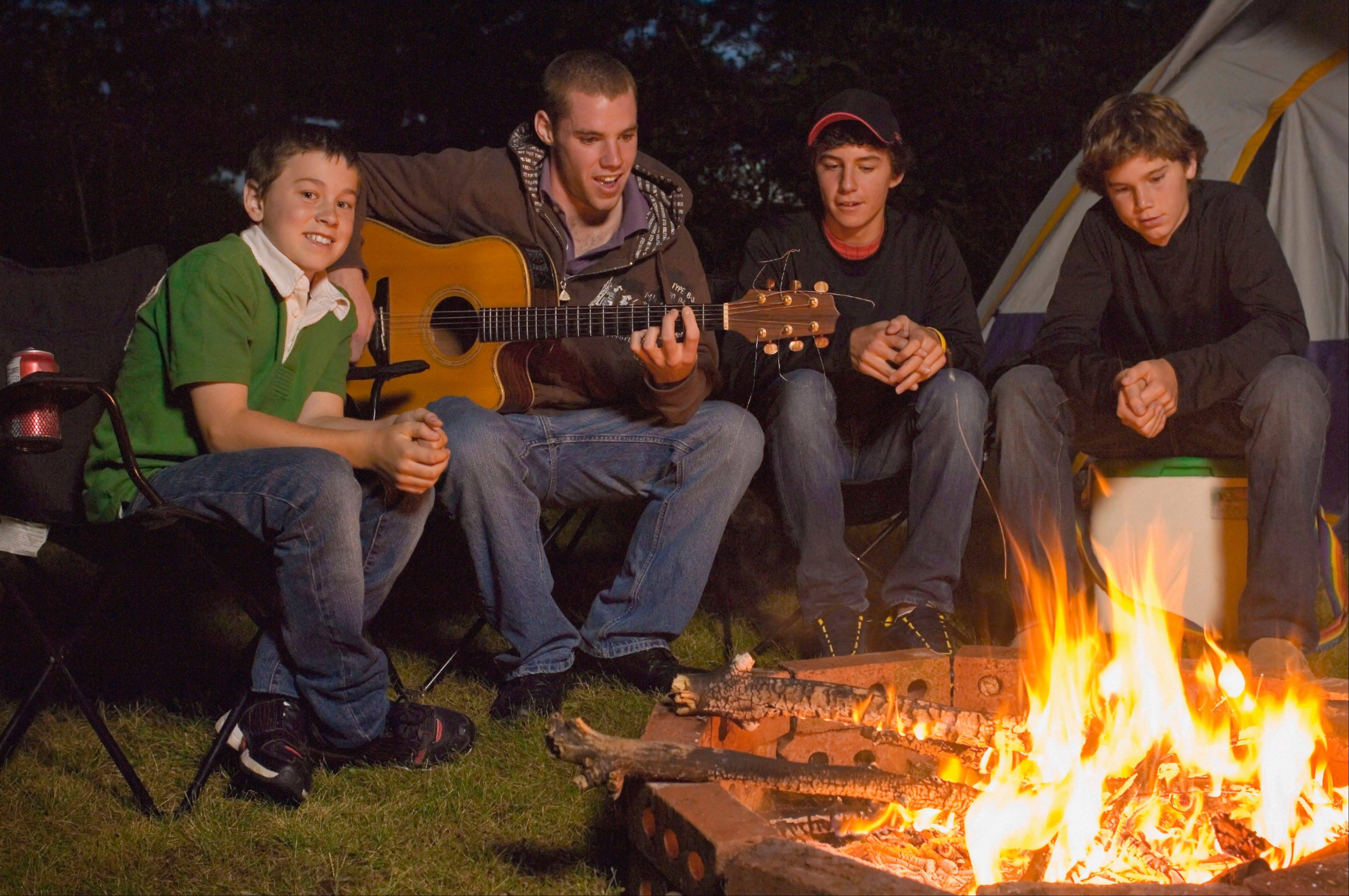 Four teenage boys sitting by campfire