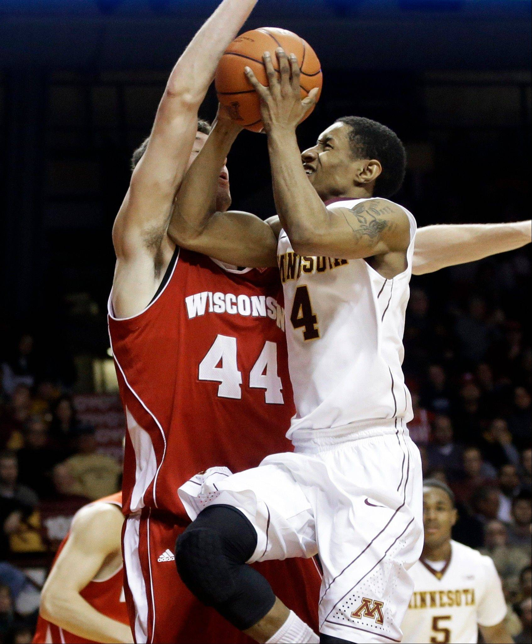 Minnesota's Deandre Mathieu, right, drives into Wisconsin's Frank Kaminsky, left, in the second half of an NCAA college basketball game, Wednesday, Jan. 22, 2014, in Minneapolis. Mathieu and Maurice Walker each scored 18 points to lead Minnesota in their 81-68 win.