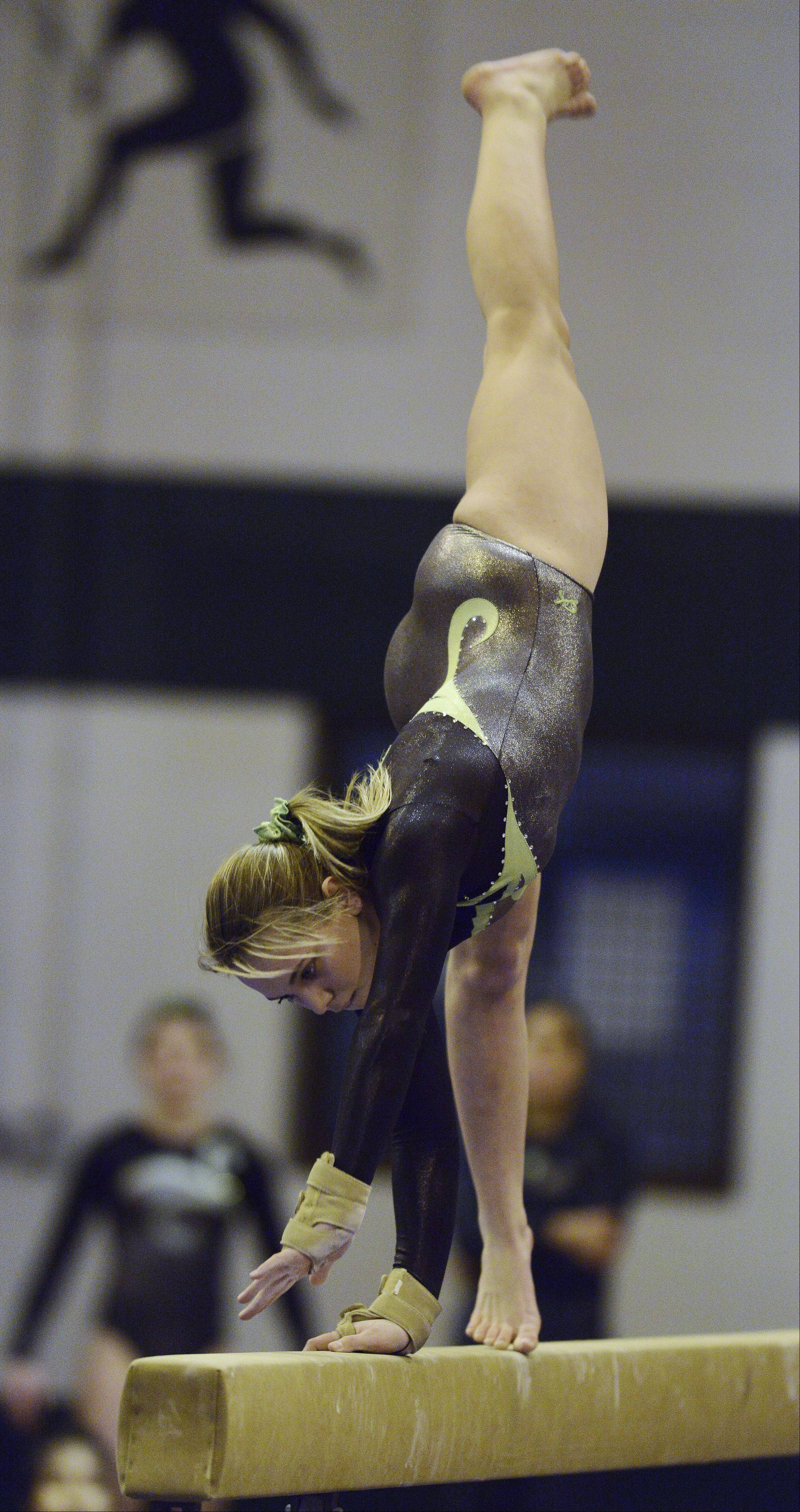 Elk Grove's Anna Bonder competes on the balance beam during Wednesday's meet with Buffalo Grove and Prospect.