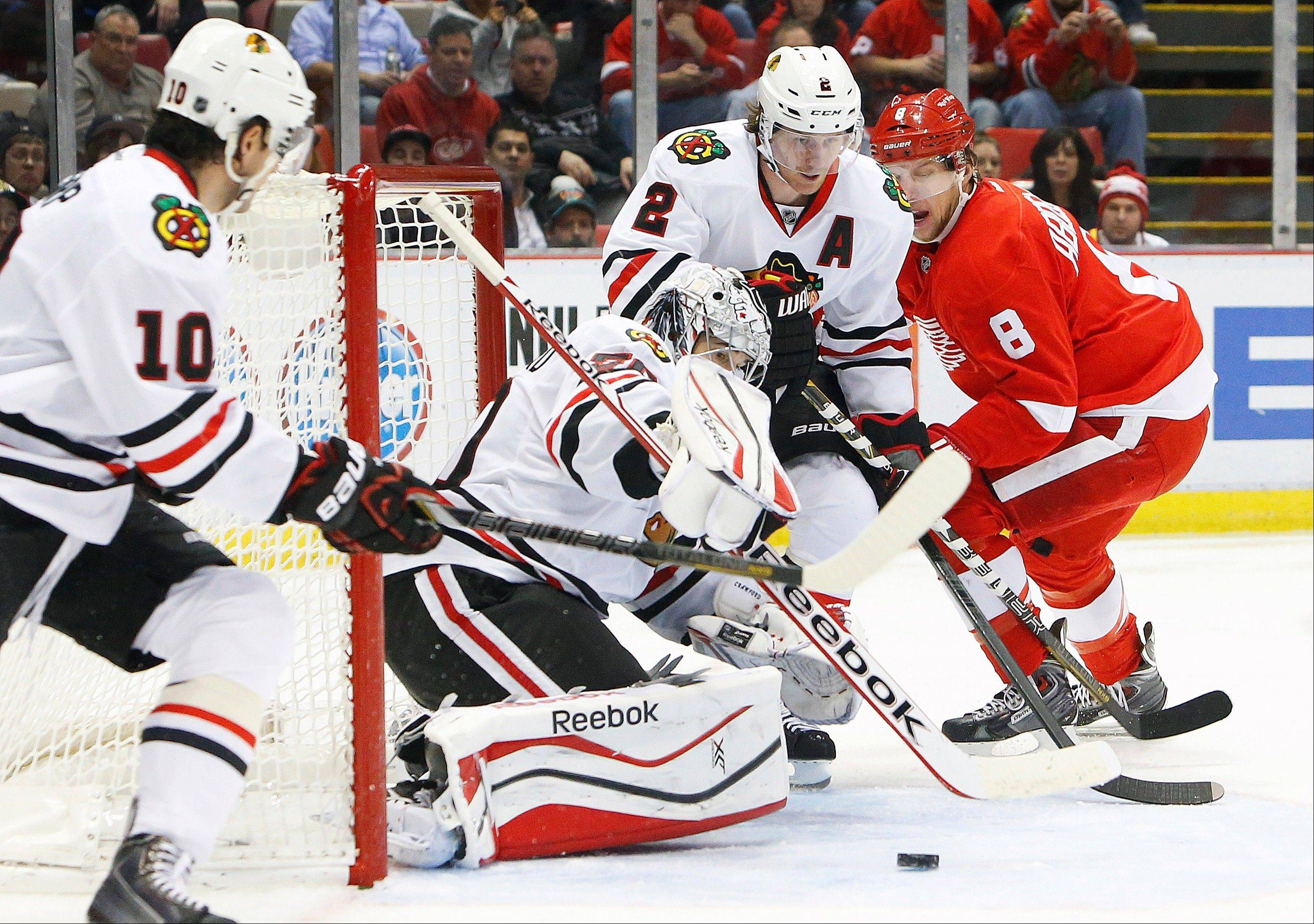 Chicago Blackhawks goalie Corey Crawford, second from left, stops a Detroit Red Wings left wing Justin Abdelkader's (8) shot in the second period of an NHL hockey game Wednesday, Jan. 22, 2014, in Detroit.