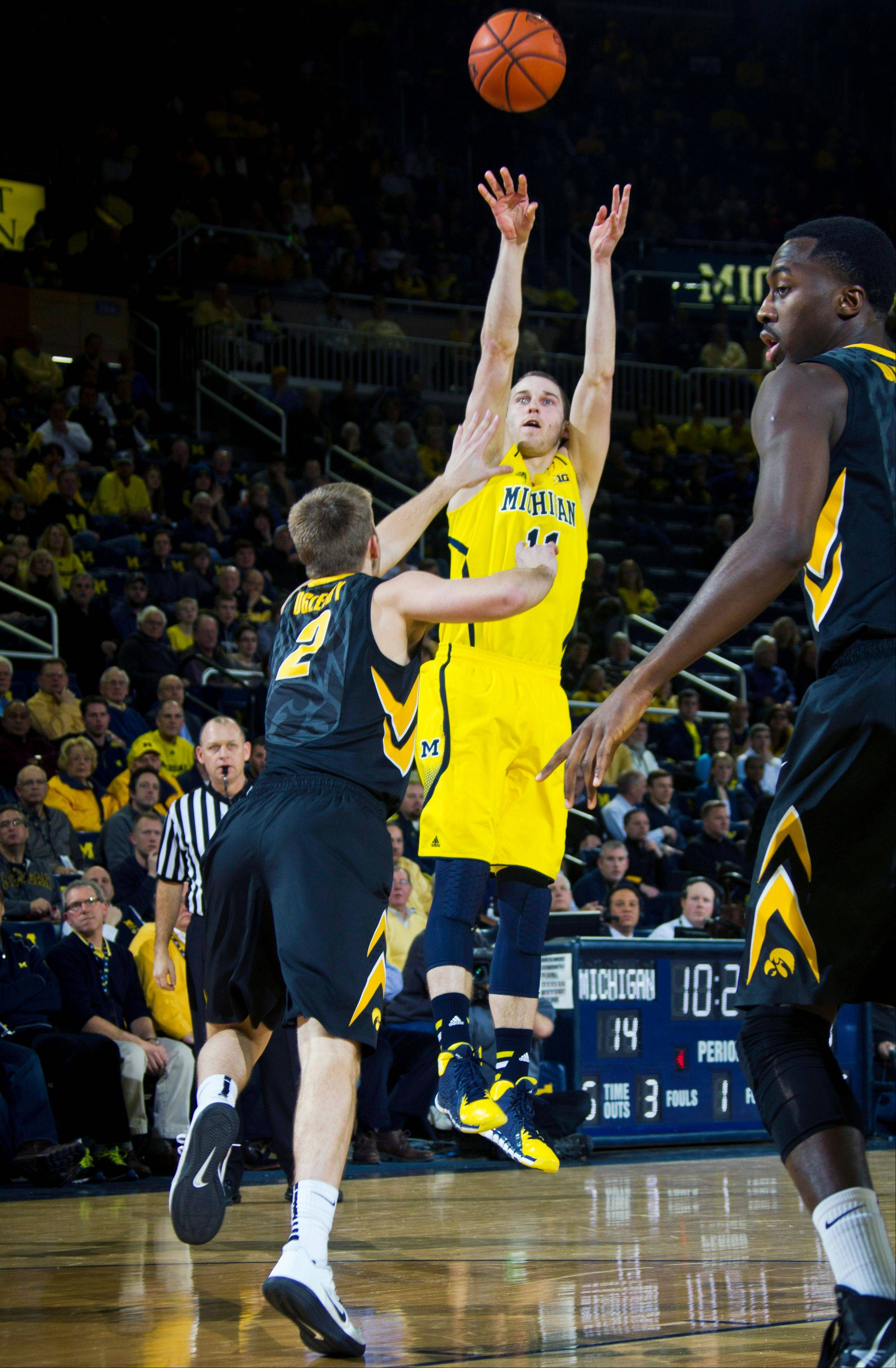 Iowa guard Josh Oglesby (2) defends a 3-pointer from Michigan guard Nik Stauskas in the first half of an NCAA college basketball game in Ann Arbor, Mich., Wednesday, Jan. 22, 2014.
