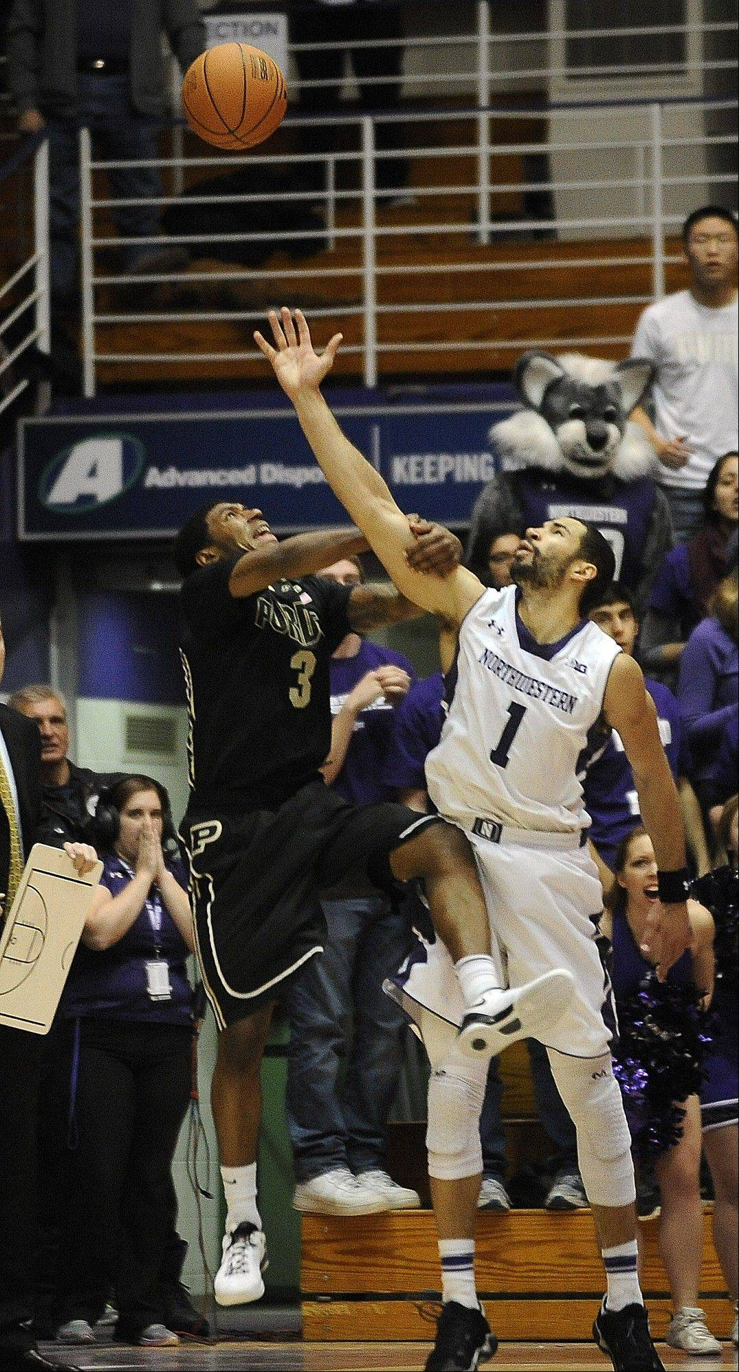 Associated PressNorthwestern guard/forward Drew Crawford (1) blocks a final second shot by Purdue guard Ronnie Johnson (3) at the end of an NCAA college basketball game Tuesday in Evanston. Northwestern won 63-60.
