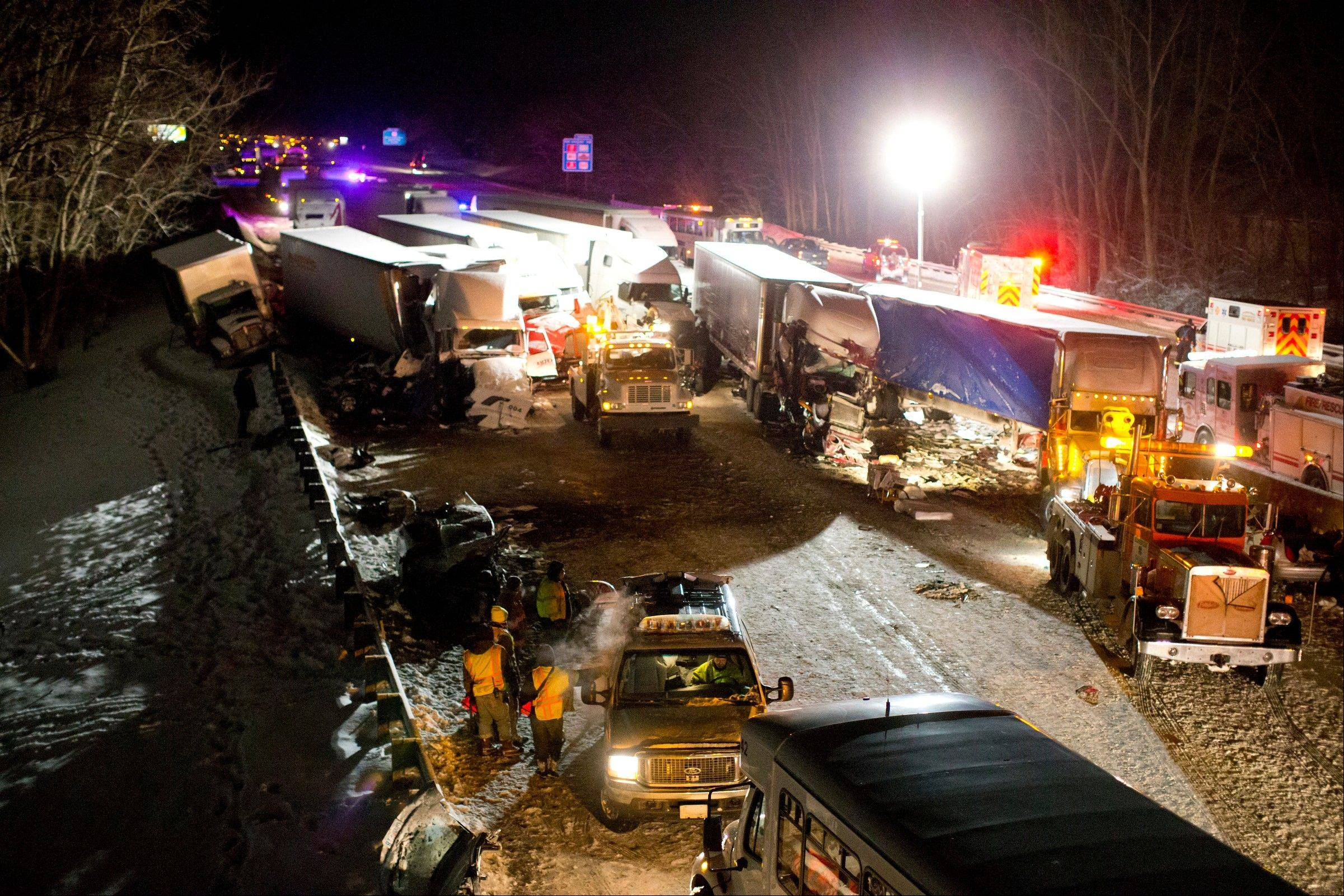 Emergency crews work at the scene of a massive pileup involving more than 40 vehicles, many of them semitrailers, along Interstate 94 Thursday afternoon, Jan. 23, 2014 near Michigan City, Ind. At least three were killed and more than 20 people were injured.