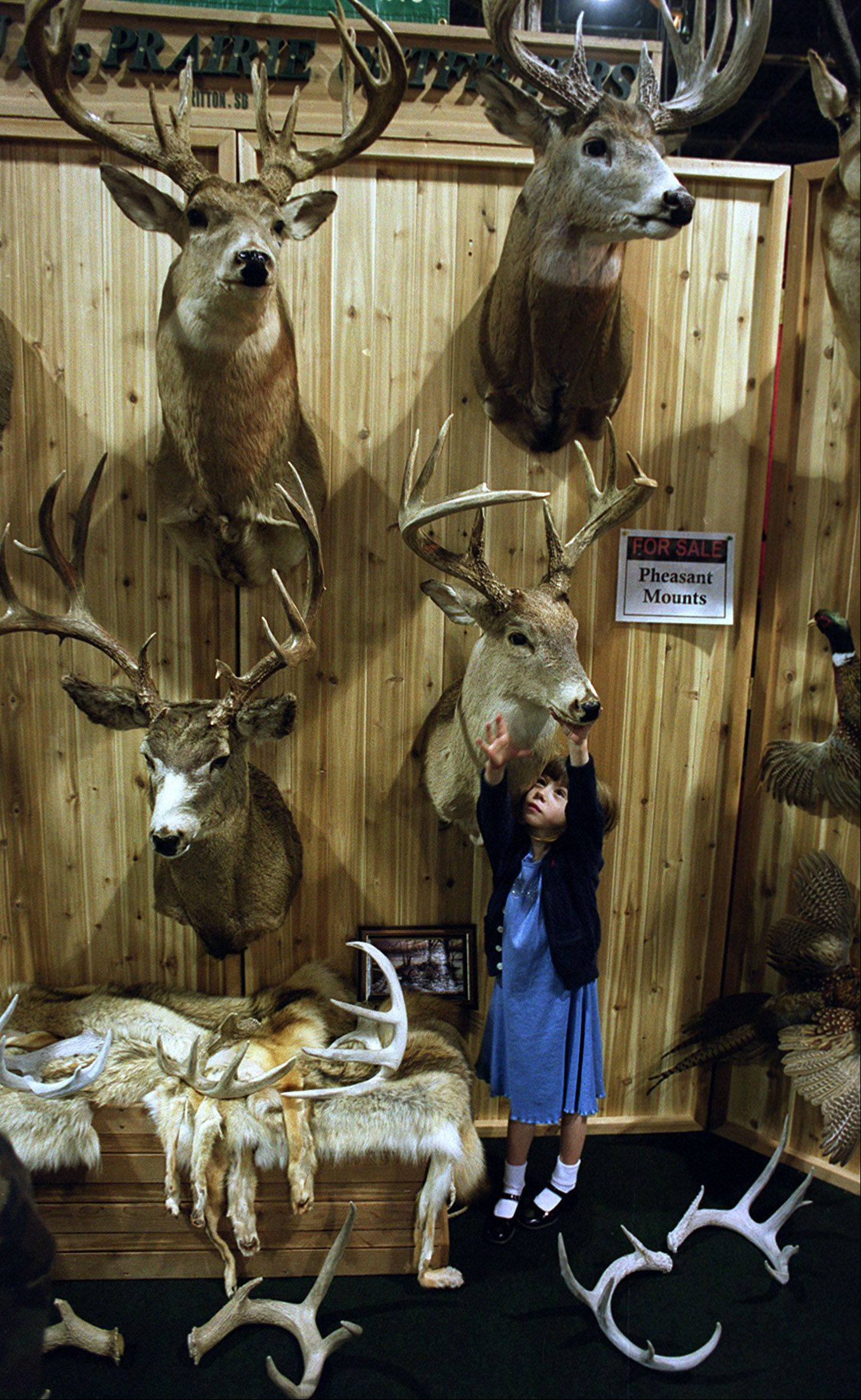Kelsey Siegel of Evanston visits the booth of Jim Mundt, Coteaudes Prairie Outfitters of South Dakota, during the Chicagoland Outdoors Show.