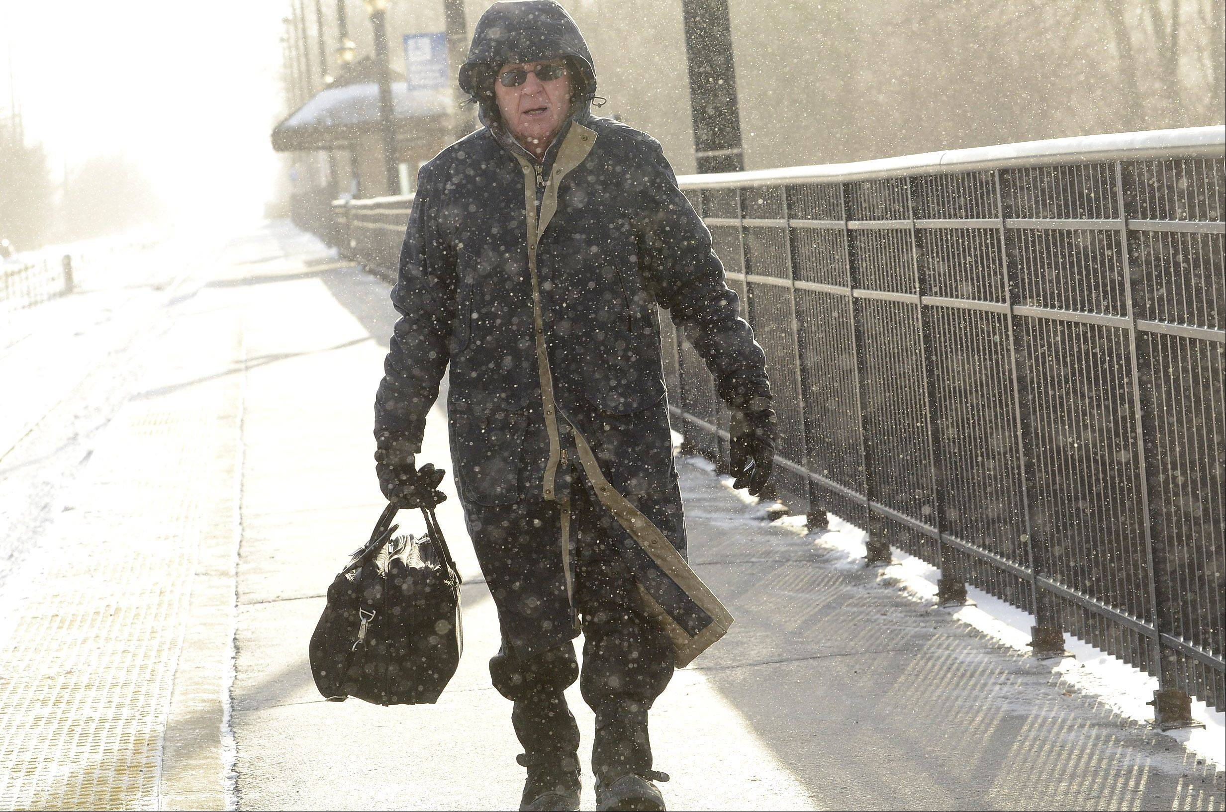 Alan Guernsey of Tower Lakes makes his way in the freezing cold to the Barrington Metra station train platform Thursday morning, on his way to his job in Chicago.