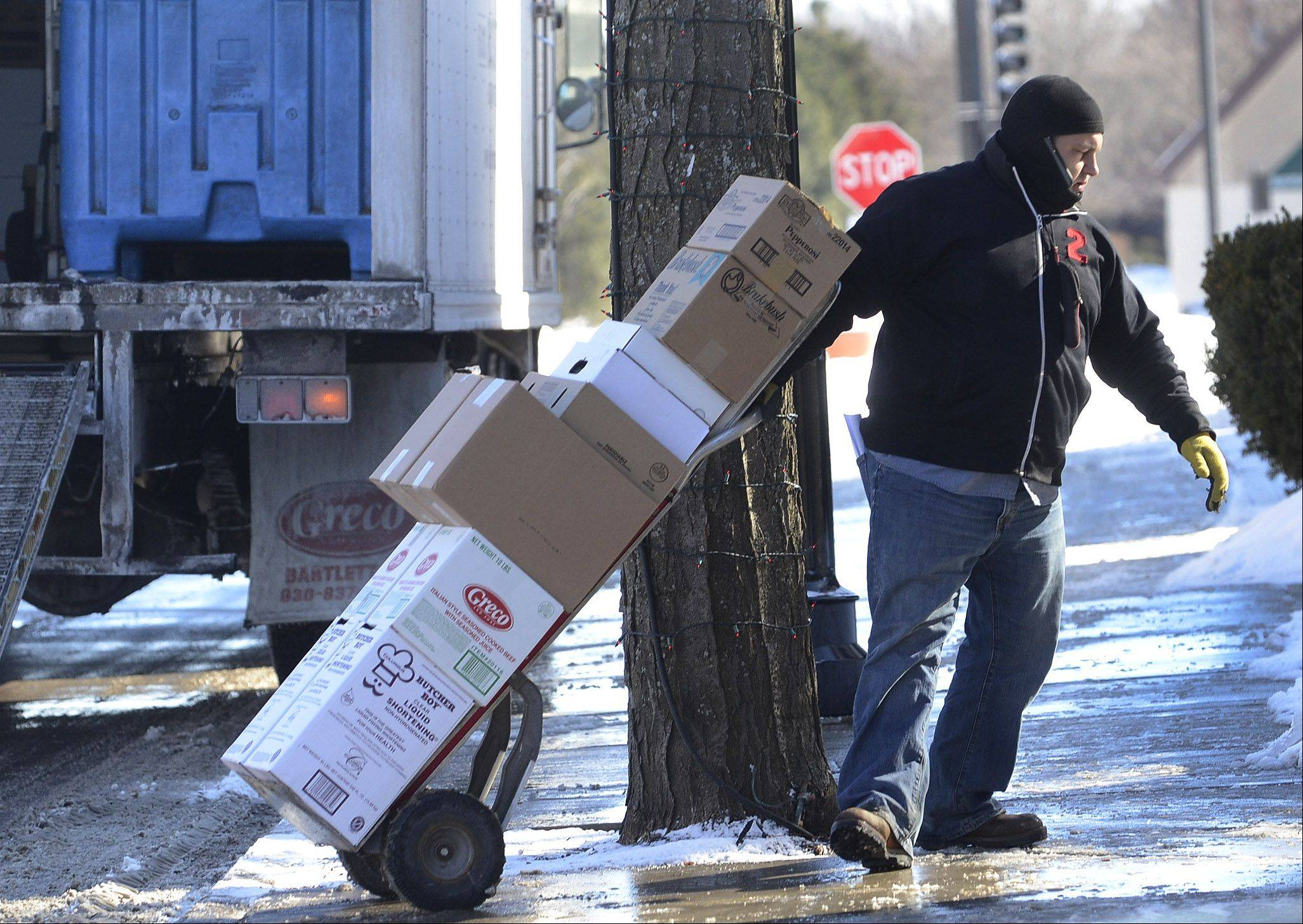 "Rocco Cataldo of Bartlett makes a food delivery Thursday in downtown Palatine. When asked how he's dealing with working in the cold, he said, ""It feels like summer compared to the last one,"" referring to the subzero temperatures we had earlier in January."