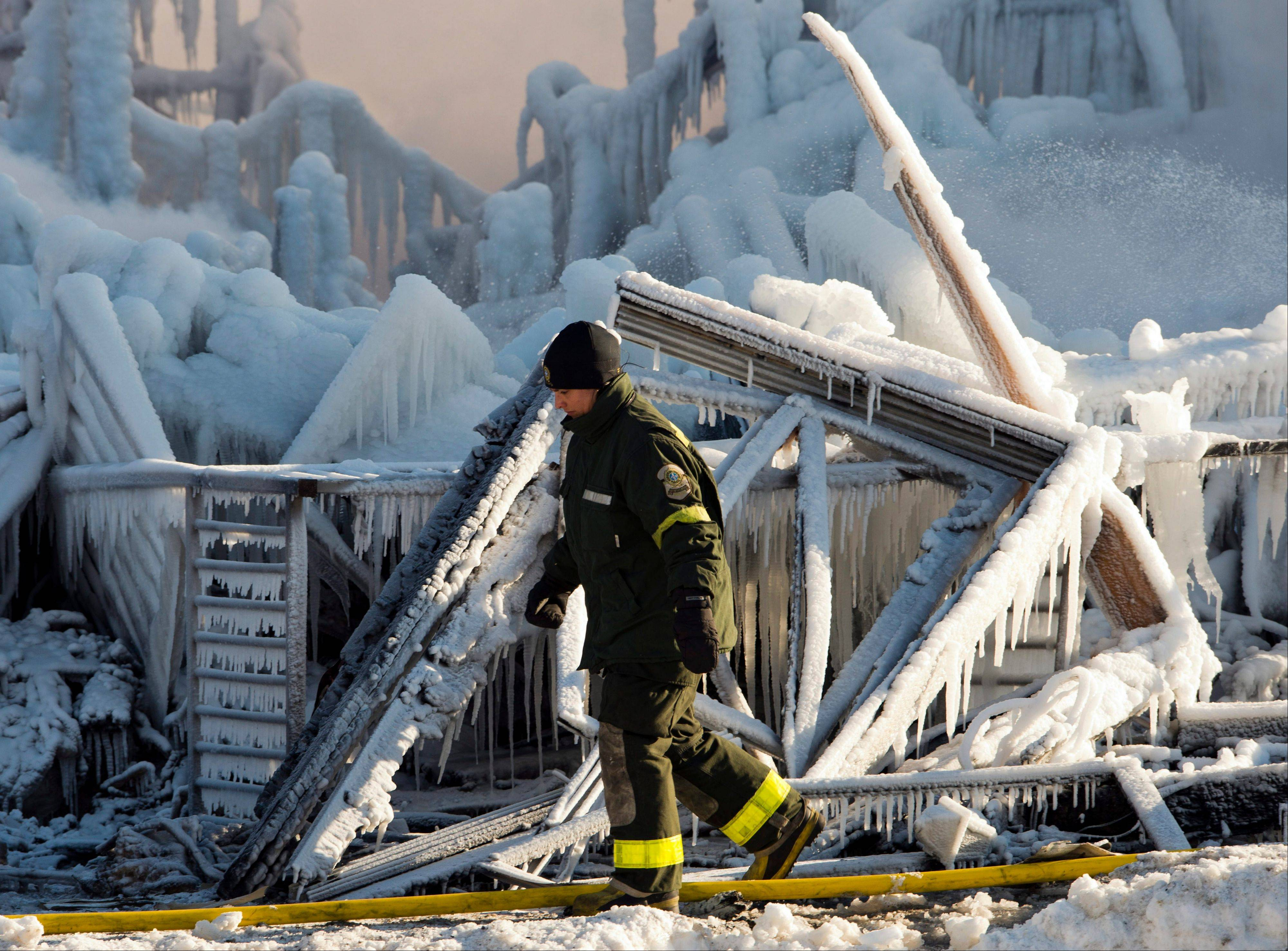A police investigator looks over the frozen rubble after a fire destroyed a seniors residence in L'Isle-Verte, Que., Thursday. The fire trapped terrified residents, most of them dependent on wheelchairs and walkers and left three confirmed dead and 30 missing.