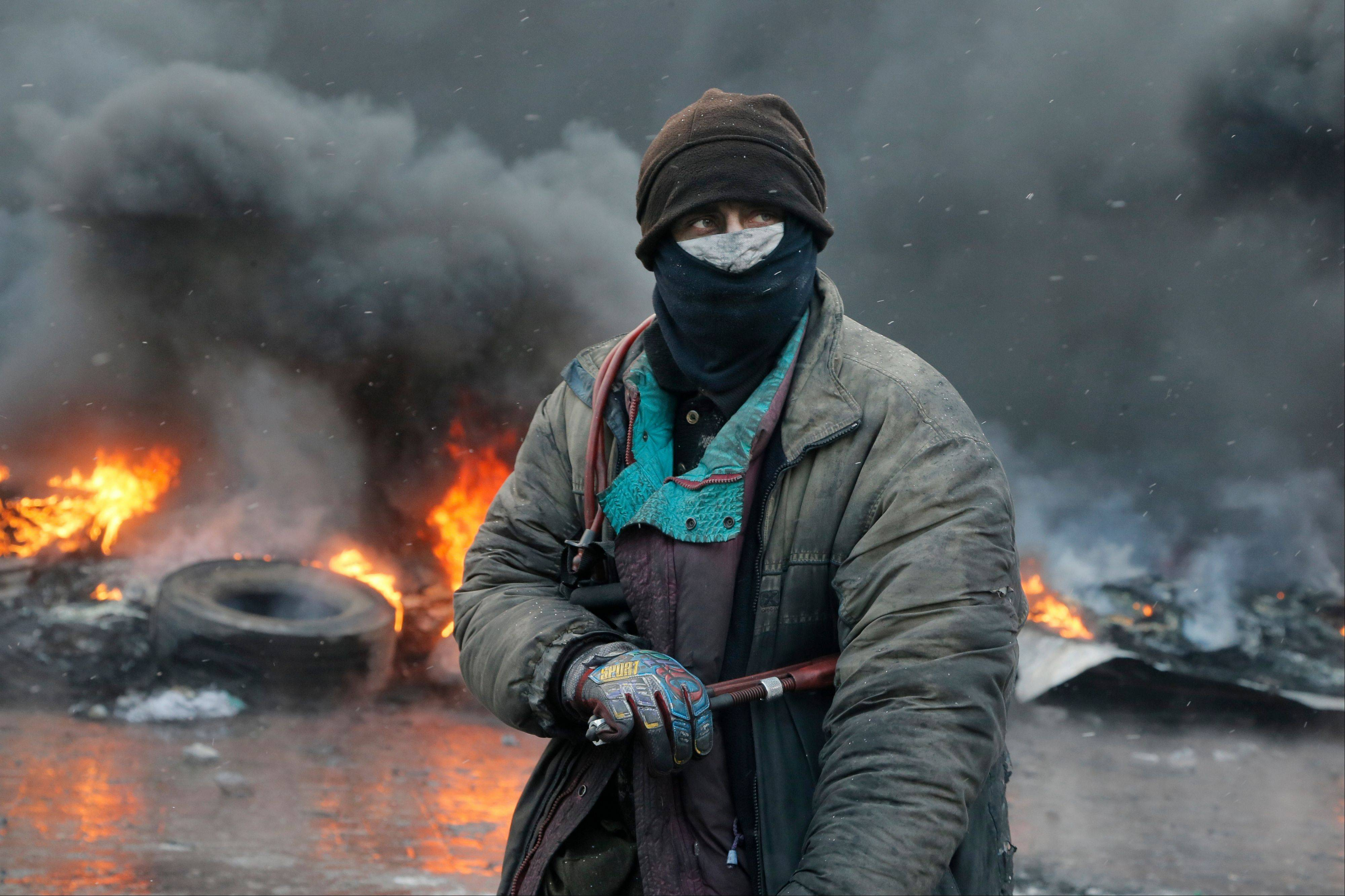 A protester stands at a burning barricades between police and protesters in central Kiev, Ukraine, Thursday. Thick black smoke from burning tires engulfed parts of downtown Kiev as an ultimatum issued by the opposition to the president to call early election or face street rage was set to expire with no sign of a compromise on Thursday.