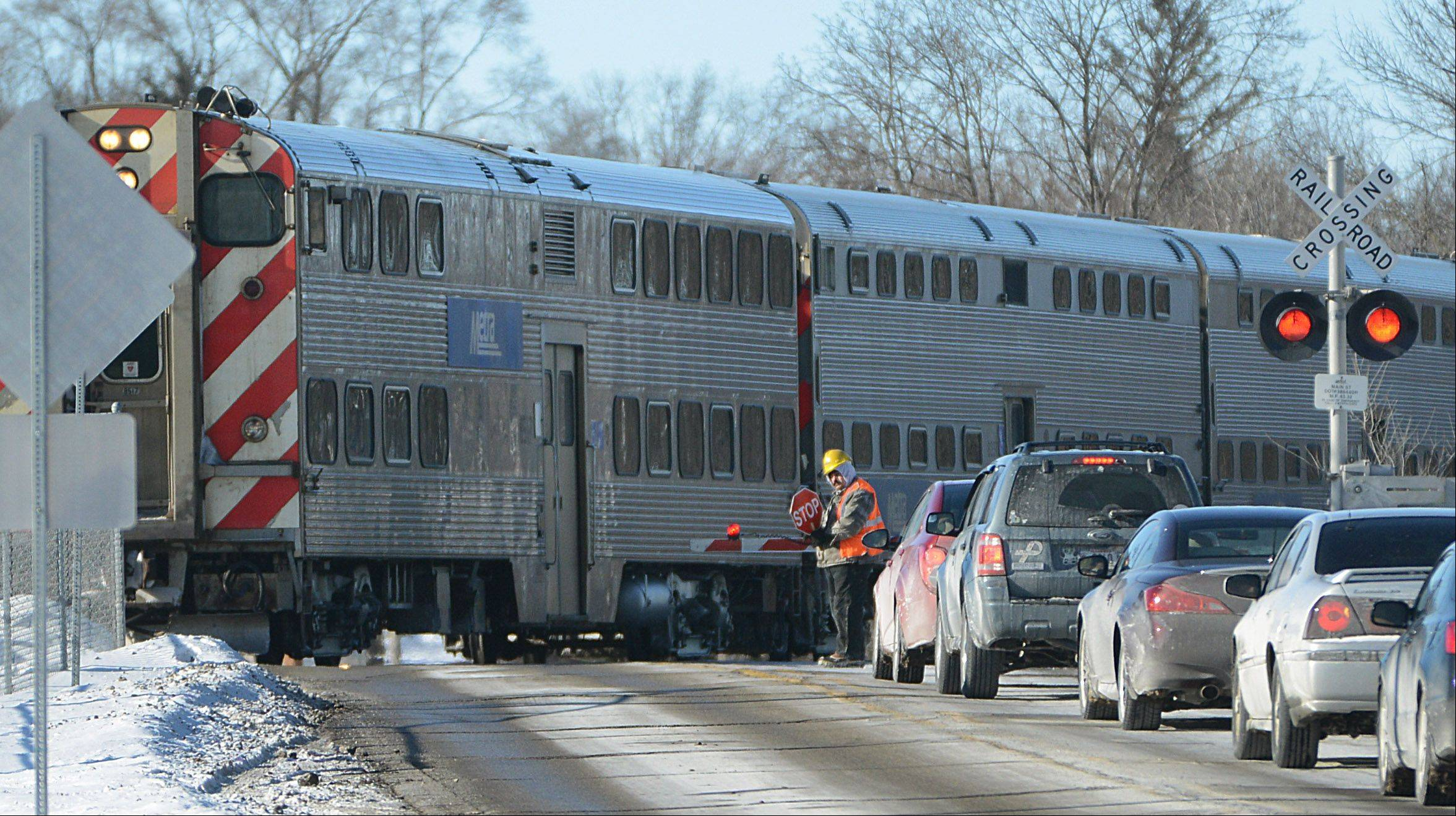A train passes by railroad officials Thursday as they investigate a fatal crash involving a vehicle and Metra train at the Route 134 crossing in Round Lake Park. A man and his daughter were killed in the crash Wednesday evening.