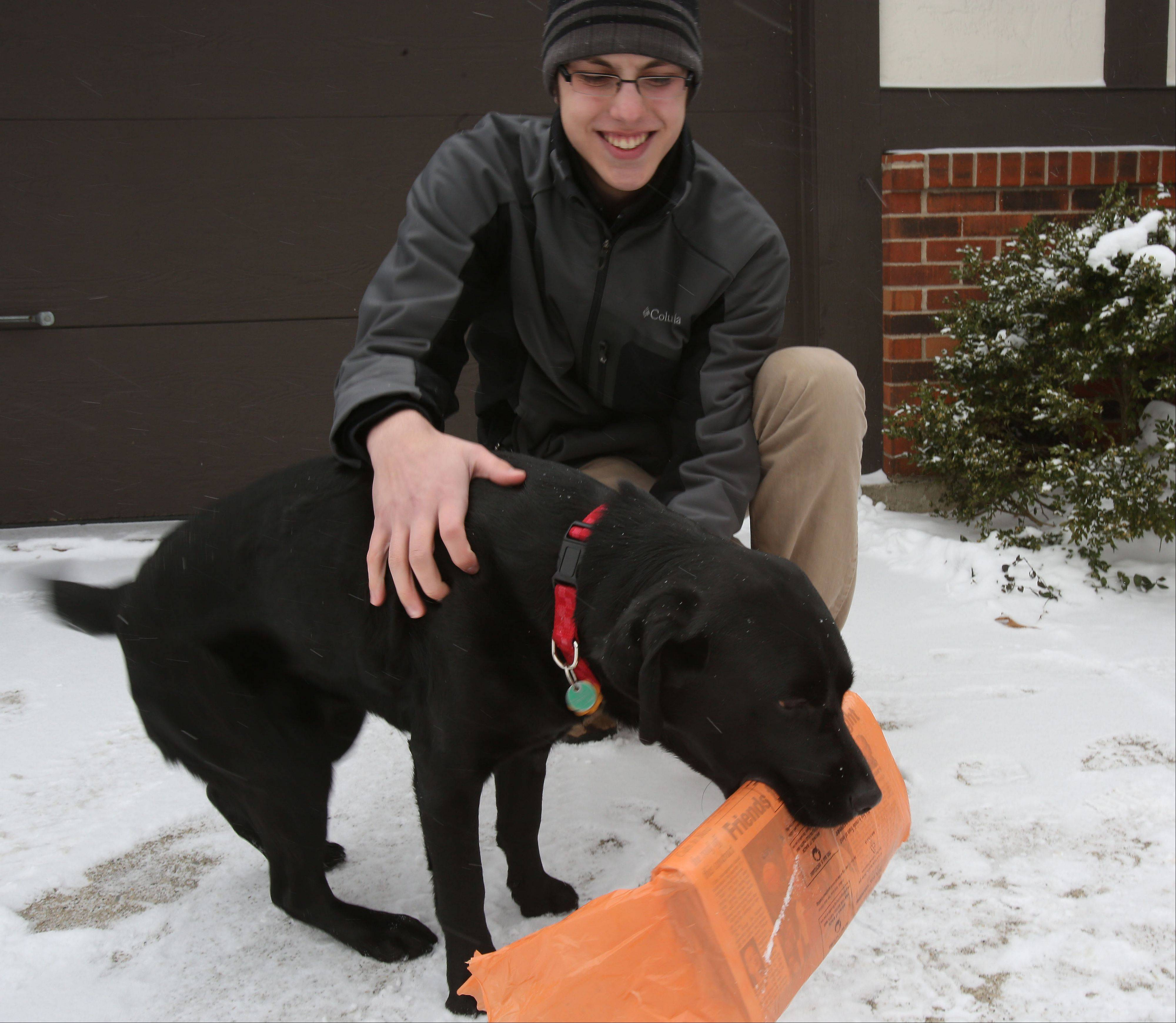 Jonathon Guse, 15, greets Morgan, who fetches the newspaper every day at their home in Glen Ellyn.