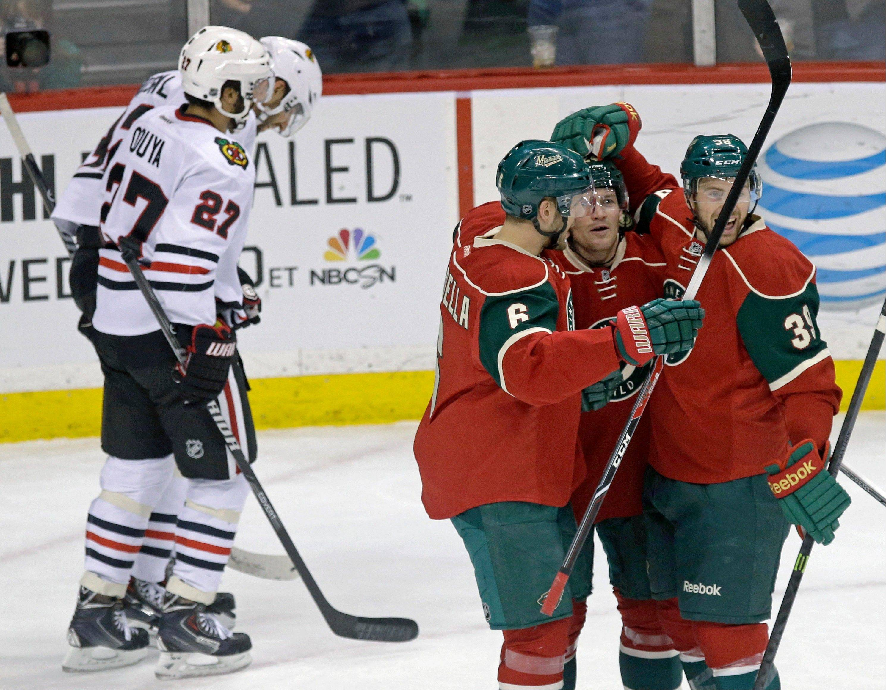 Minnesota Wild's Matt Cooke, right center, is congratulated on his goal by Marco Scandella and Nate Prosser, right, as Chicago Blackhawks' Johnny Oduya, left, of Sweden, and Michal Rozsival, skate to their bench in the first period of an NHL hockey game, Thursday, Jan. 23, 2014, in St. Paul, Minn.