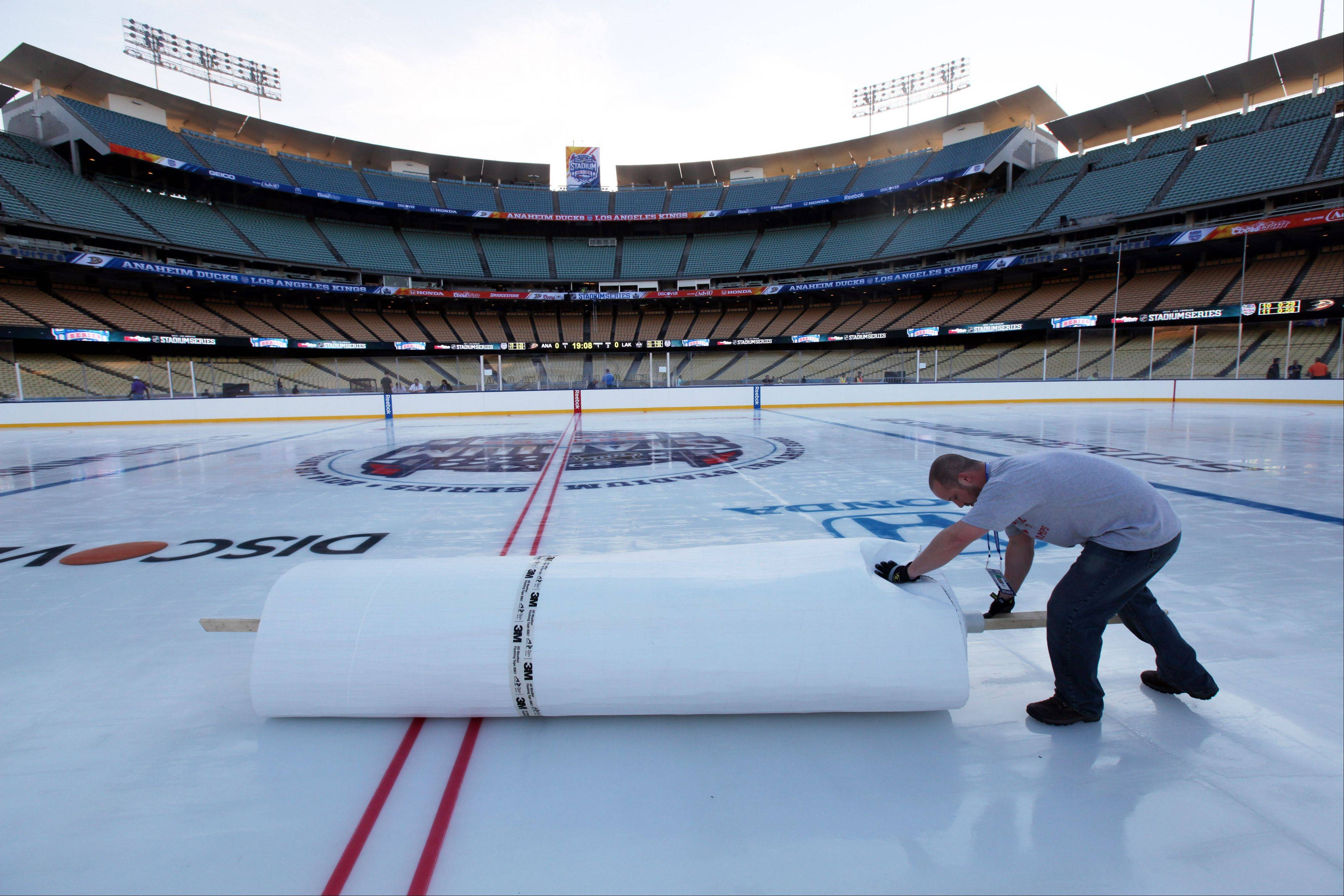 A worker rolls up mylar that protected a hockey rink at Dodger Stadium from daytime temperatures in the high 70s Fahrenheit, as preparations continue for the upcoming 2014 NHL Stadium Series hockey game in Los Angeles, Wednesday, Jan. 22, 2014. The Los Angeles Kings and Anaheim Ducks will play outdoors at Dodger Stadium next Saturday, Jan. 25th.