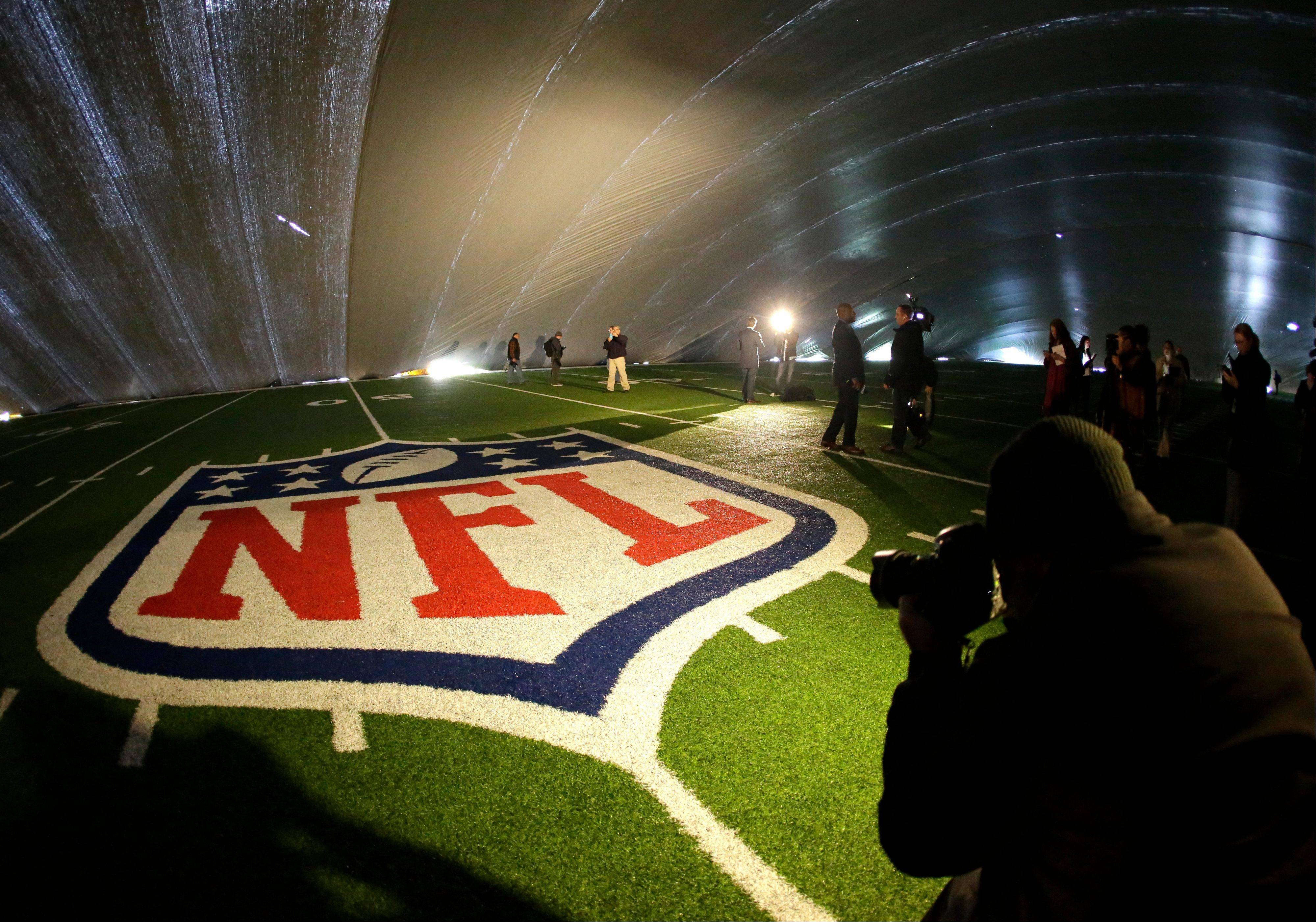 The NFL logo at midfield of MetLife Stadium is illuminated by lights on television reporters� videocameras as members of the media are given a tour under a tarp used by crews to keep the turf dry ahead of Super Bowl XLVIII in East Rutherford, N.J.