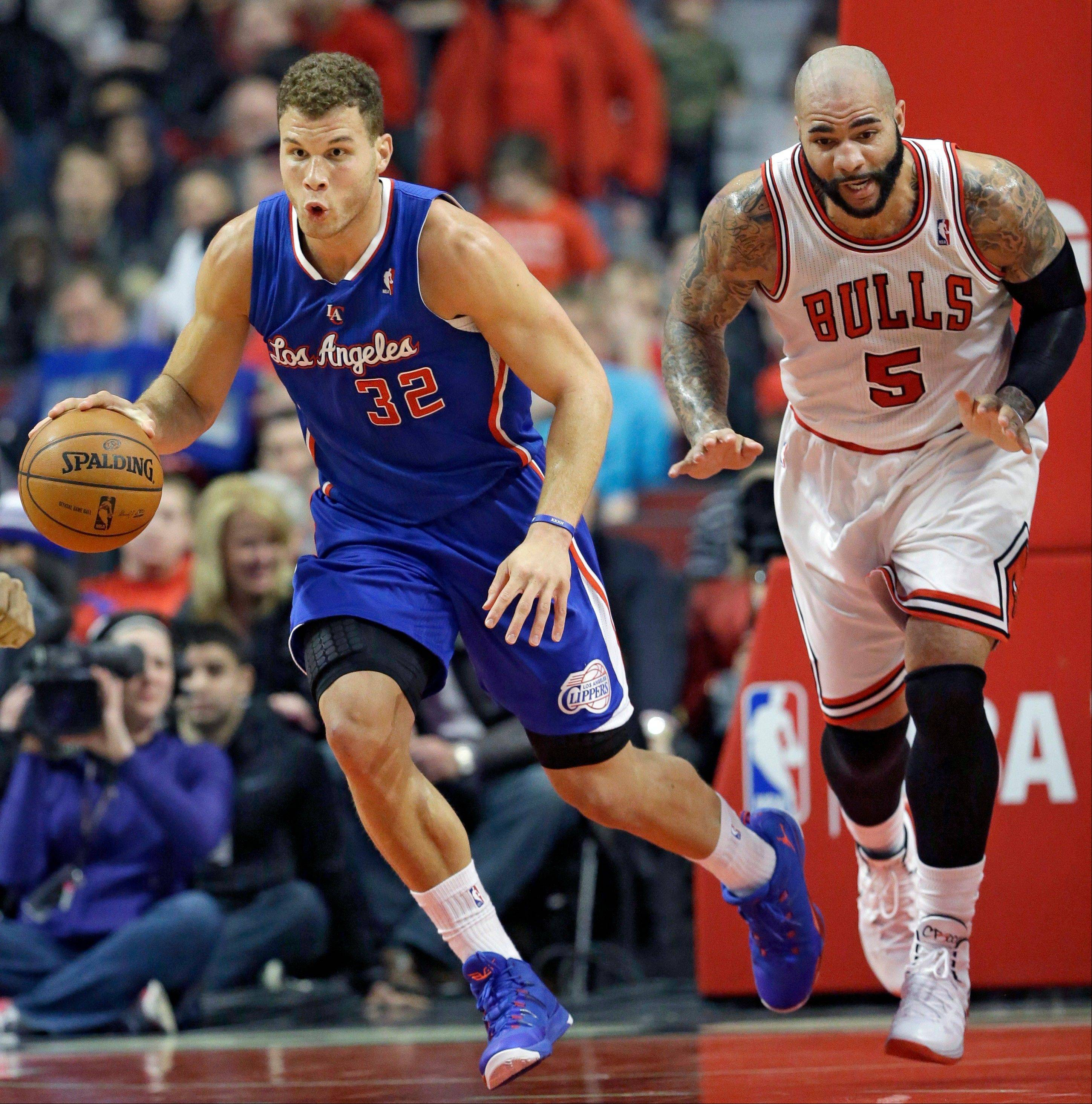 Los Angeles Clippers forward Blake Griffin, left, controls the ball against Chicago Bulls forward Carlos Boozer during Friday night�s game at the United Center.