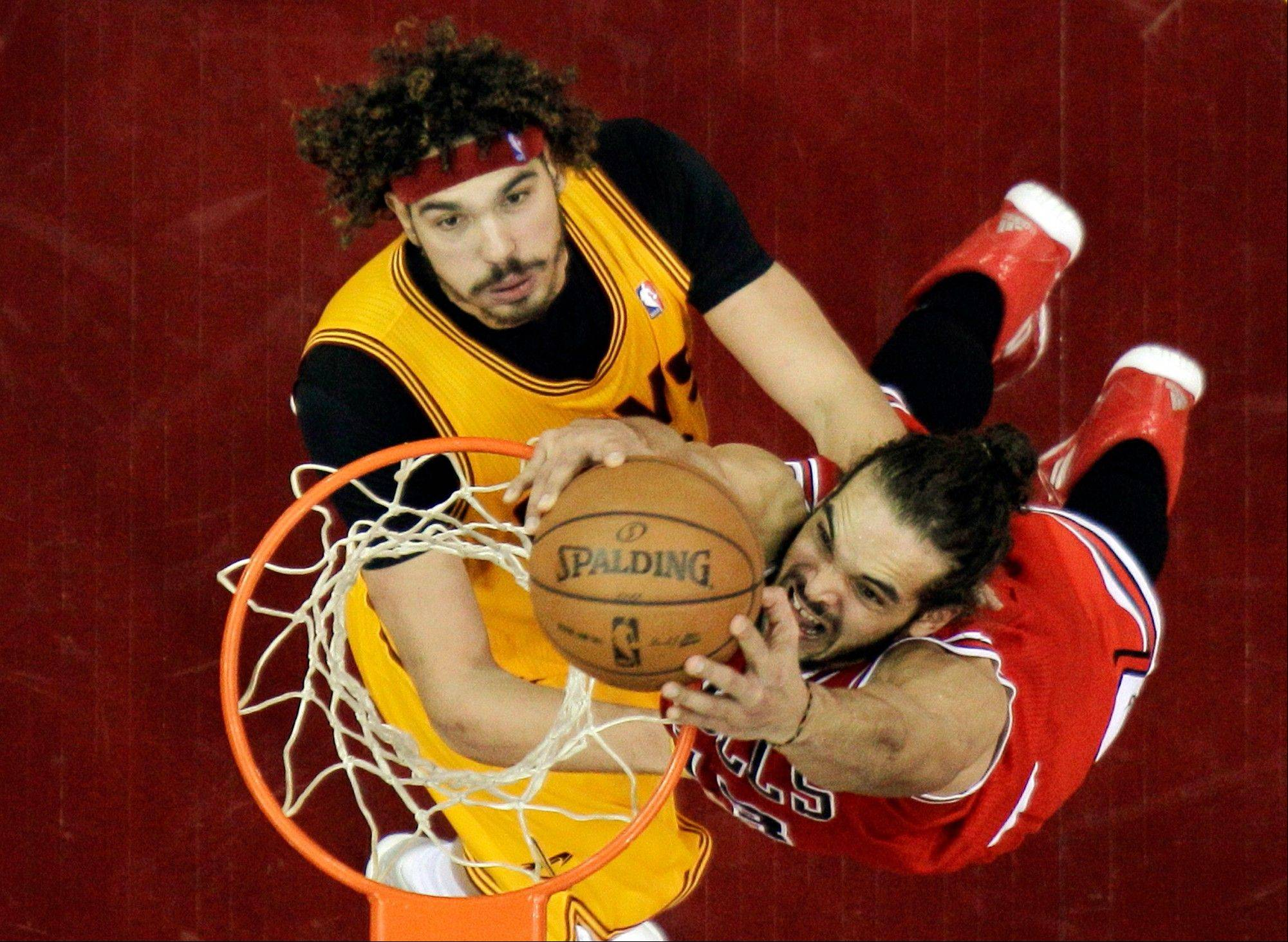 Bulls center Joakim Noah, right, dunks on Cleveland Cavaliers forward Anderson Varejao in their game Wednesday in Cleveland. The Bulls won 98-87, and Noah collected 18 rebounds.