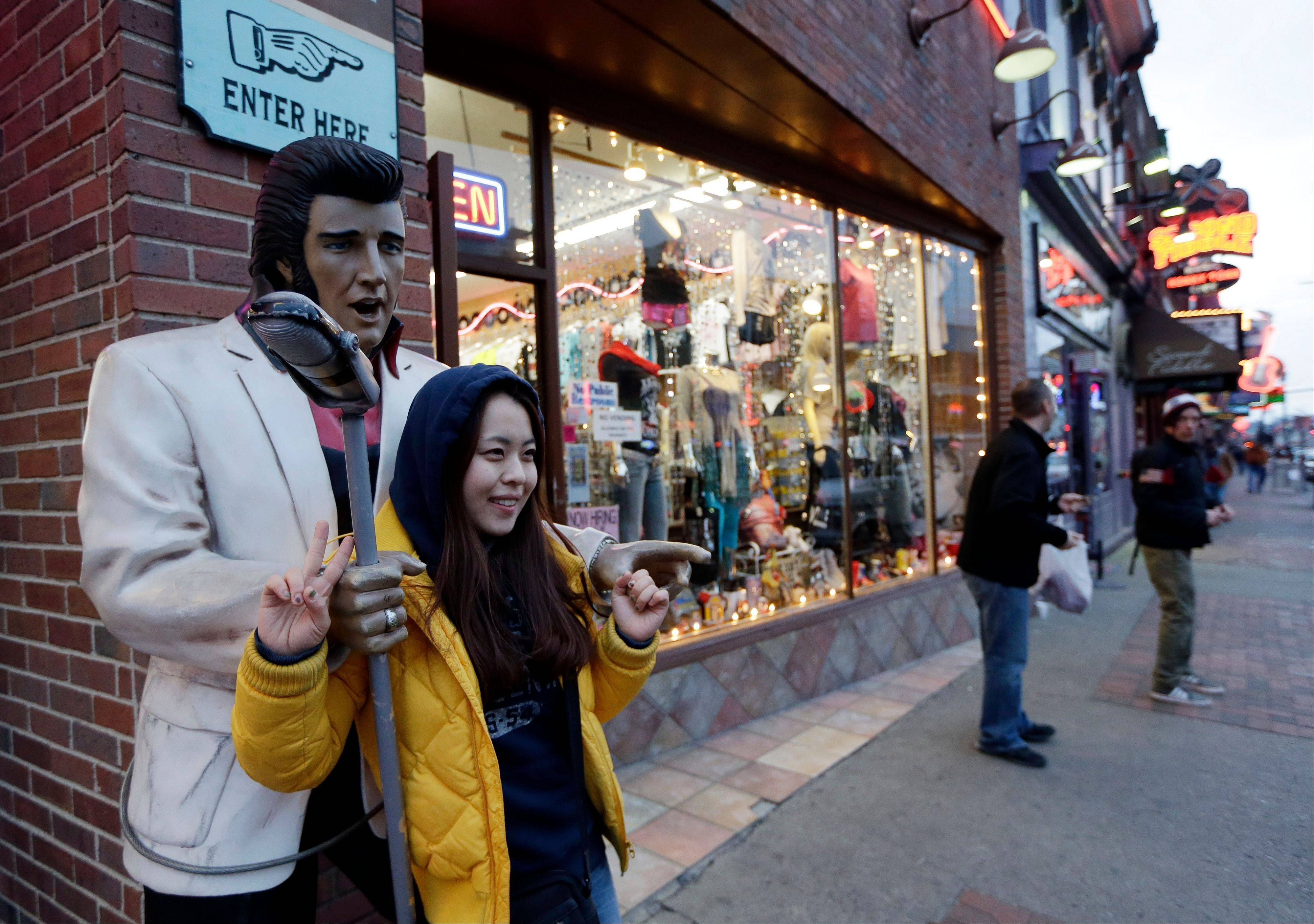 Kim Young, of Seoul, South Korea, poses for a photo by a statue of Elvis Presley while visiting Broadway in Nashville, Tenn. Broadway is lined with honky tonks, restaurants and souvenir shops.