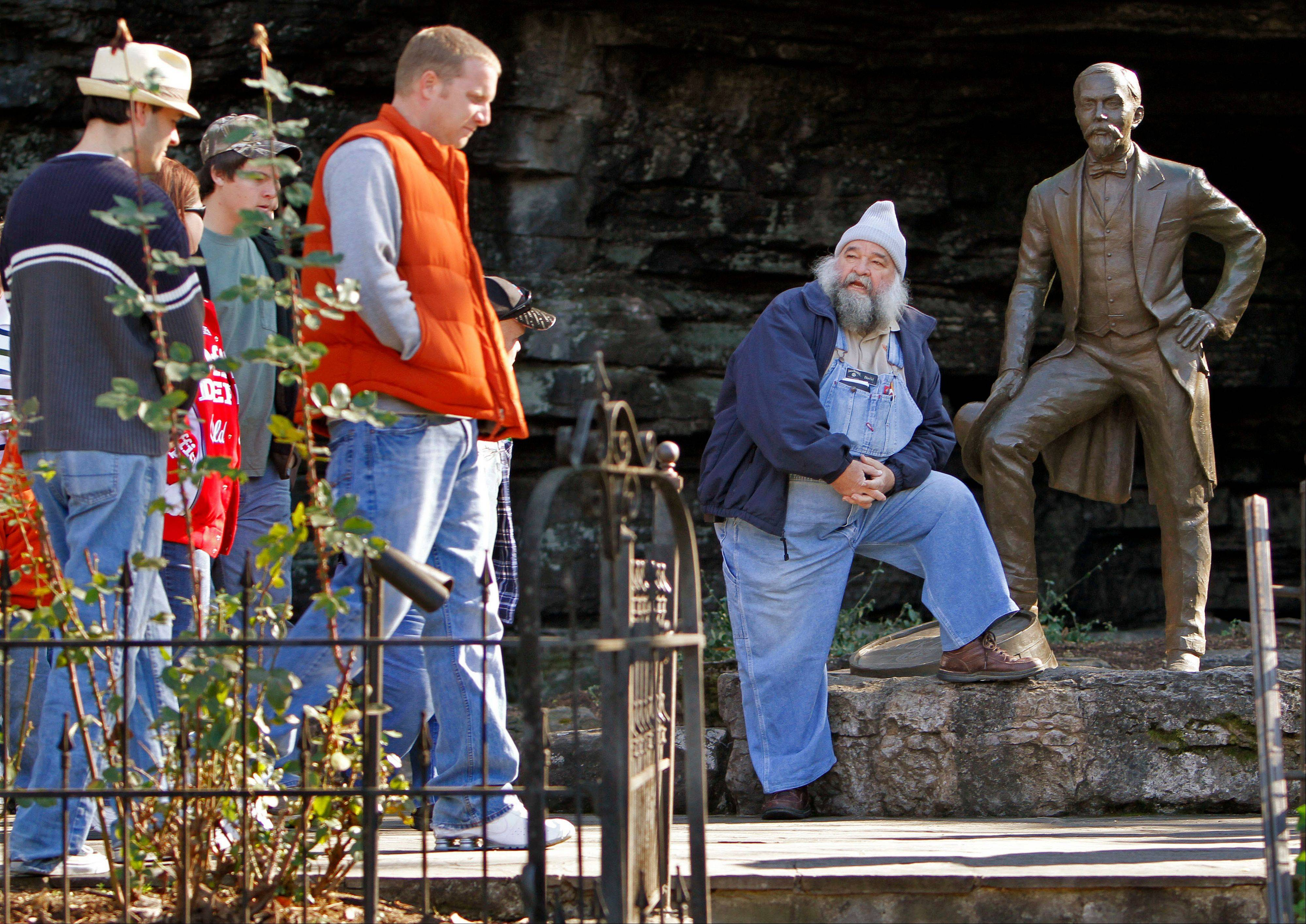 "Tour guide David ""Porky"" Roper, right, sits by a statue of Jack Daniel as he waits for the tour group he is leading to catch up to him at the Jack Daniel's distillery in Lynchburg, Tenn. The 70-mile trip from Nashville to Lynchburg offers a free tour of the oldest registered American distillery."