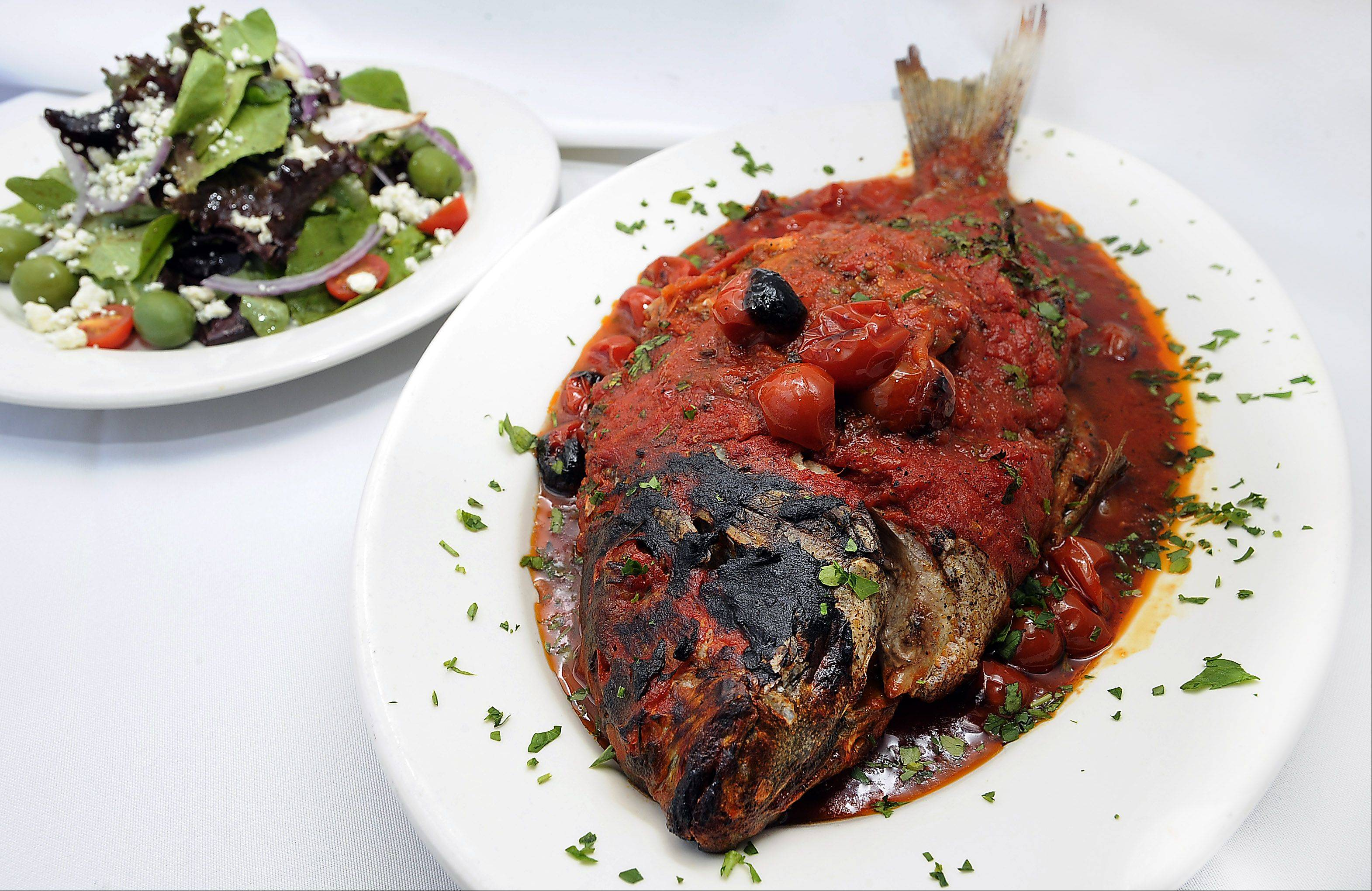 Whole sea bass gets baked with tomatoes at Enzo & Lucia in Long Grove.