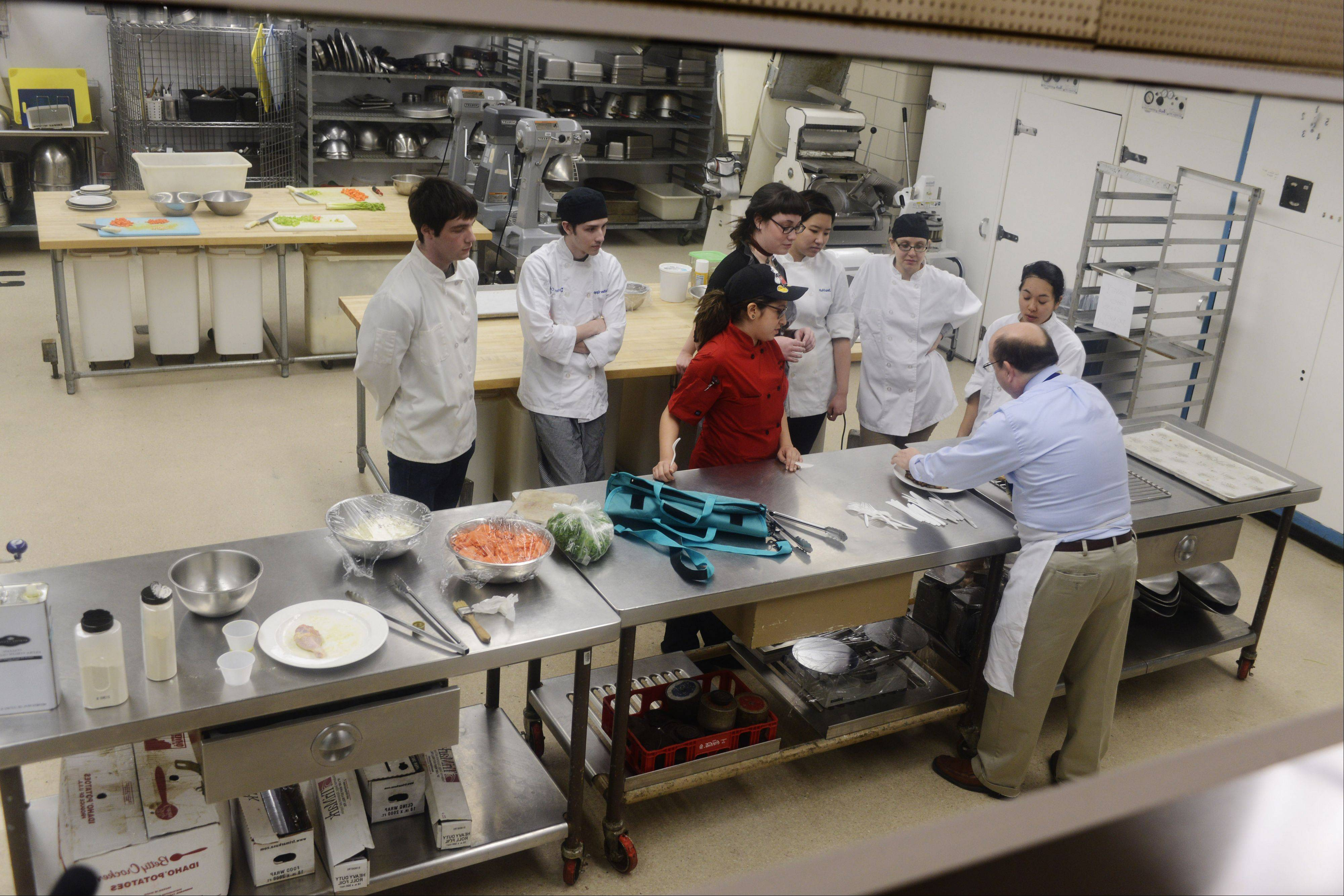 Marisa Marquez, in red, and her fellow students gather around her completed dish as Patrick Beach, head of the hospitality management program, talks about her effort in the kitchen at Harper College in Palatine.
