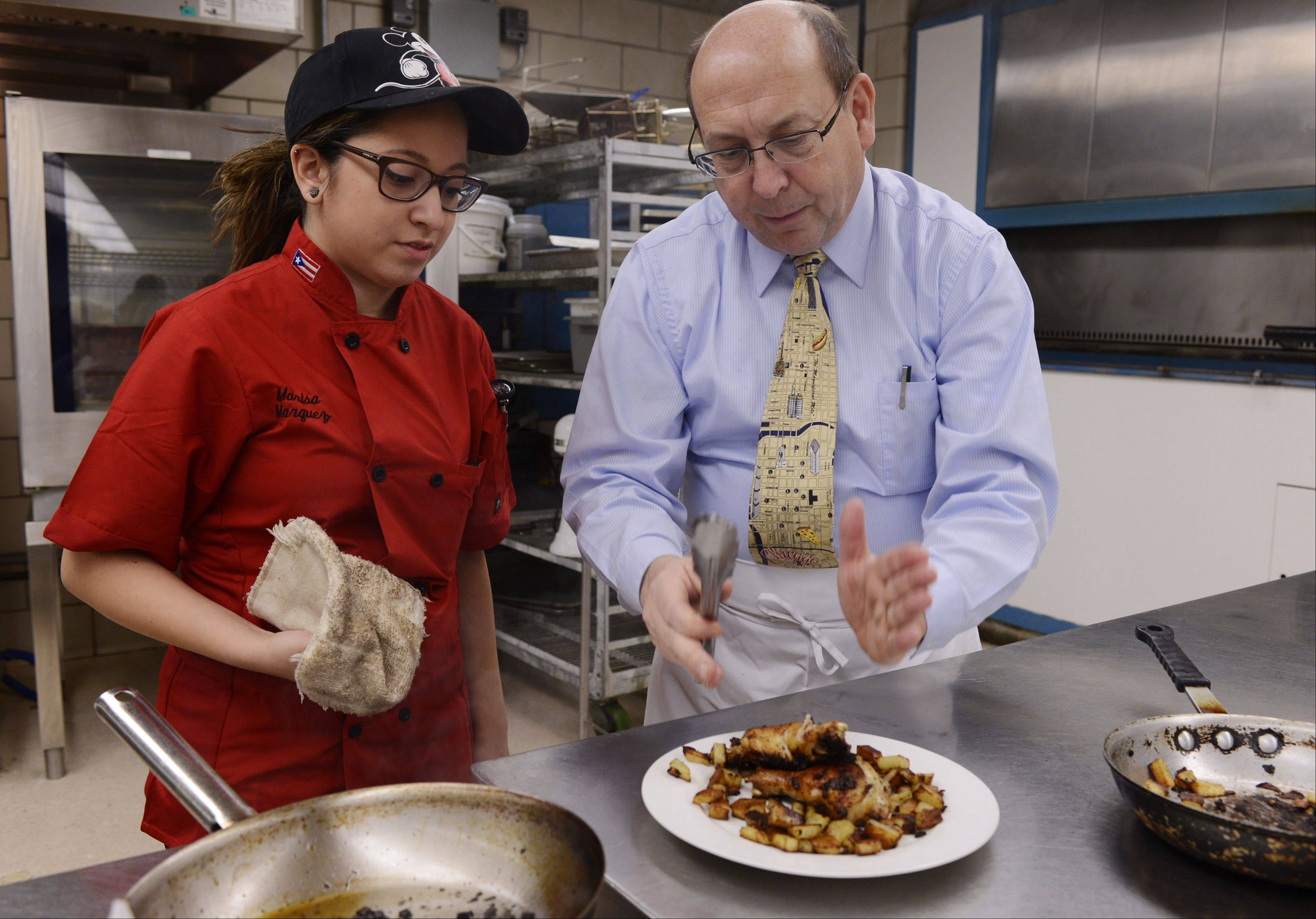 Marquez listens as Patrick Beach, head of the Hospitality Management program at Harper College, suggests a way to plate a dish in the school's kitchen.