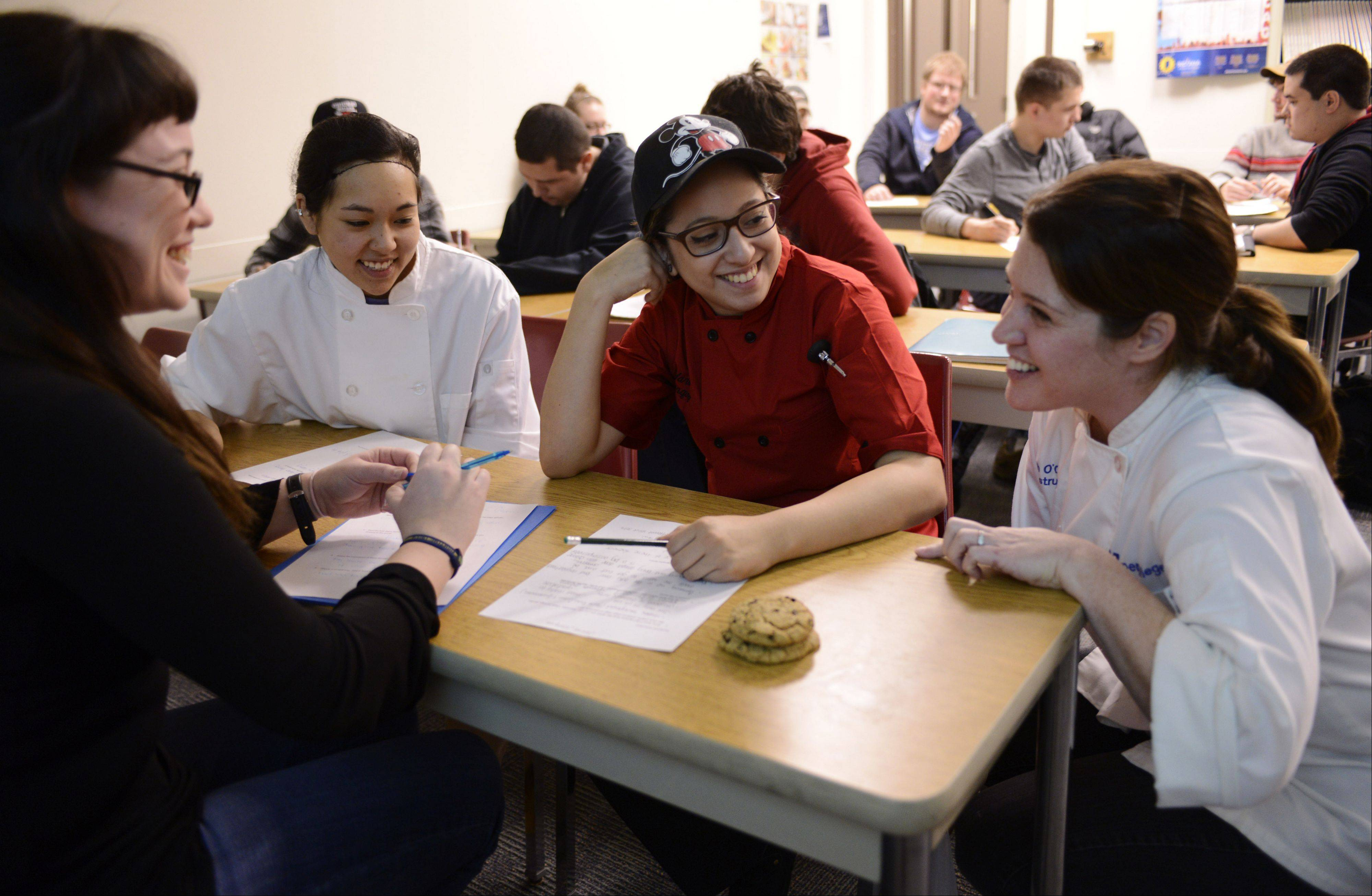 Dani Garcia of Streamwood, left, Julie ana Pak of Northbrook and Marisa Marquez of Arlington Heights talk with instructor Beth O'Connell in the classroom at Harper College in Palatine.