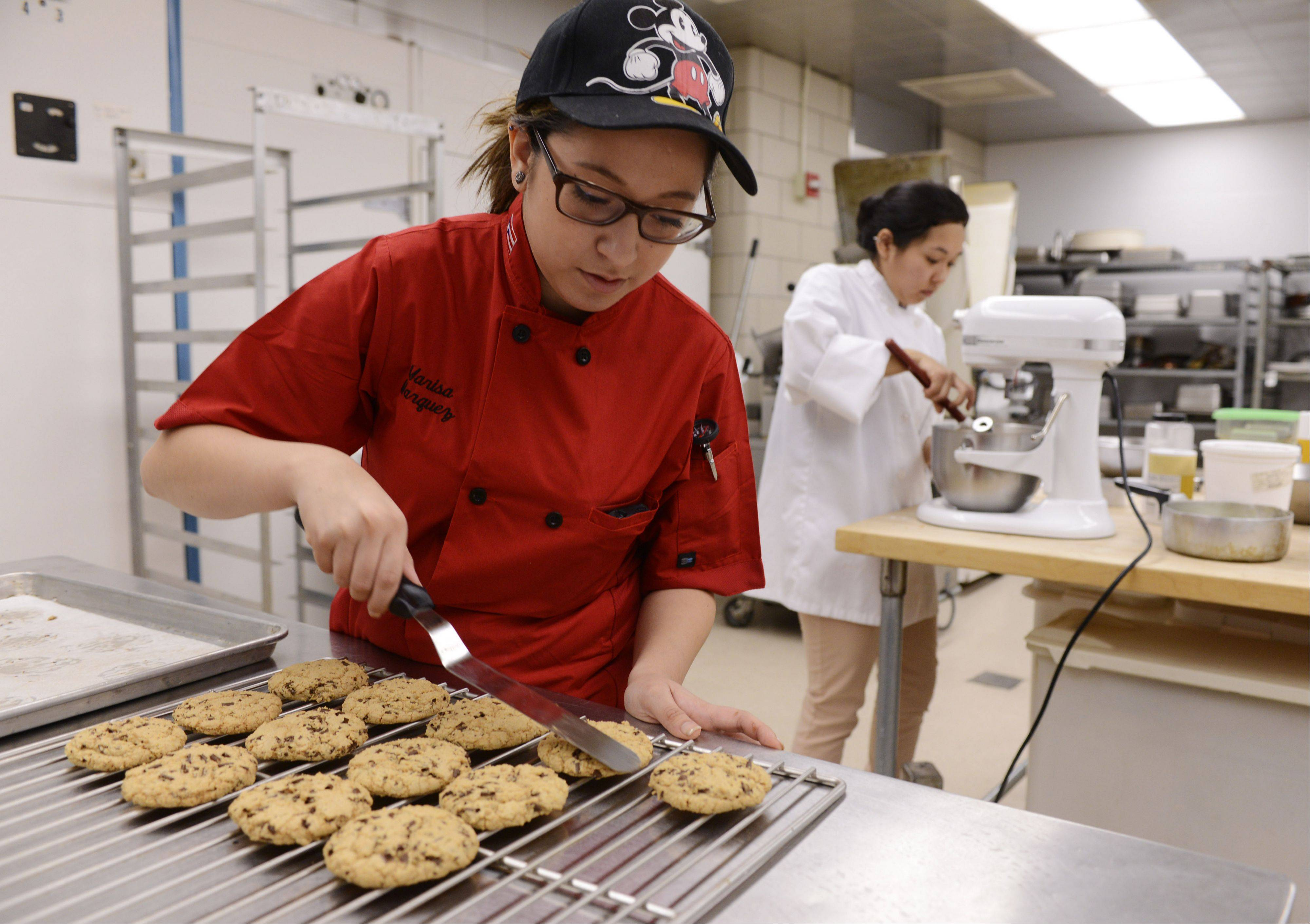 Marquez places cookies on a cooling rack in the Harper College kitchen.