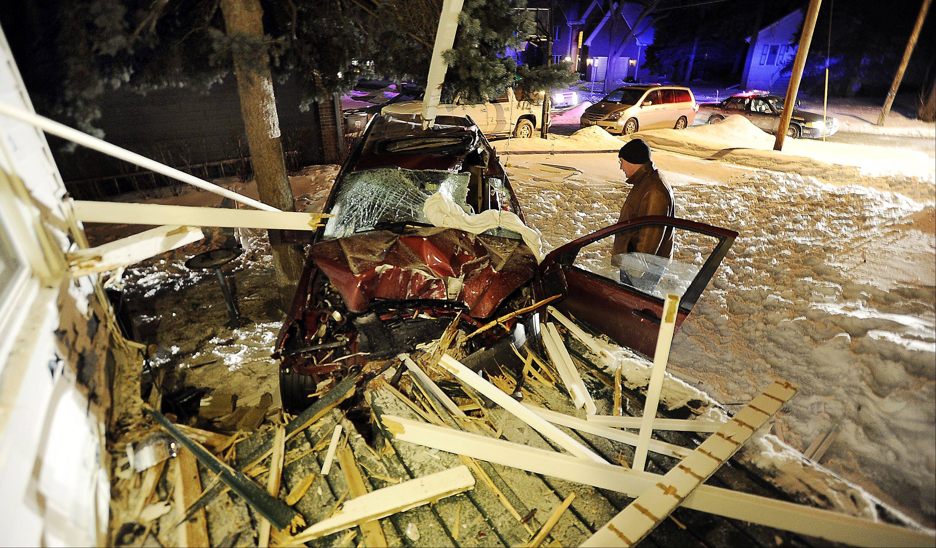 Homeowner Thomas Sarikas looks over the damage to his Arlington Heights house Thursday night after an SUV crashed into it.