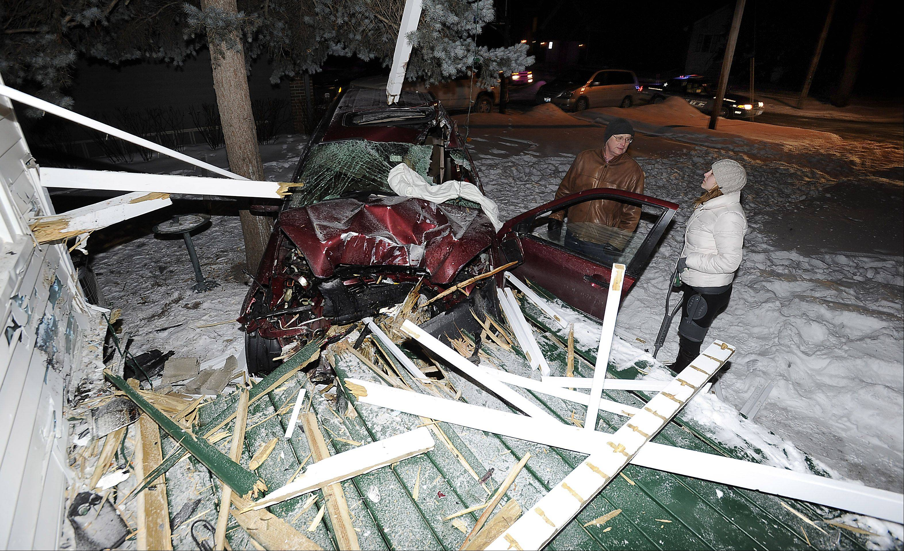 Homeowner Thomas Sarikas and his daughter Chelsea look over the damage caused when an SUV slammed into their house Thursday night in Arlington Heights. The driver was injured and had to be cut from the vehicle.