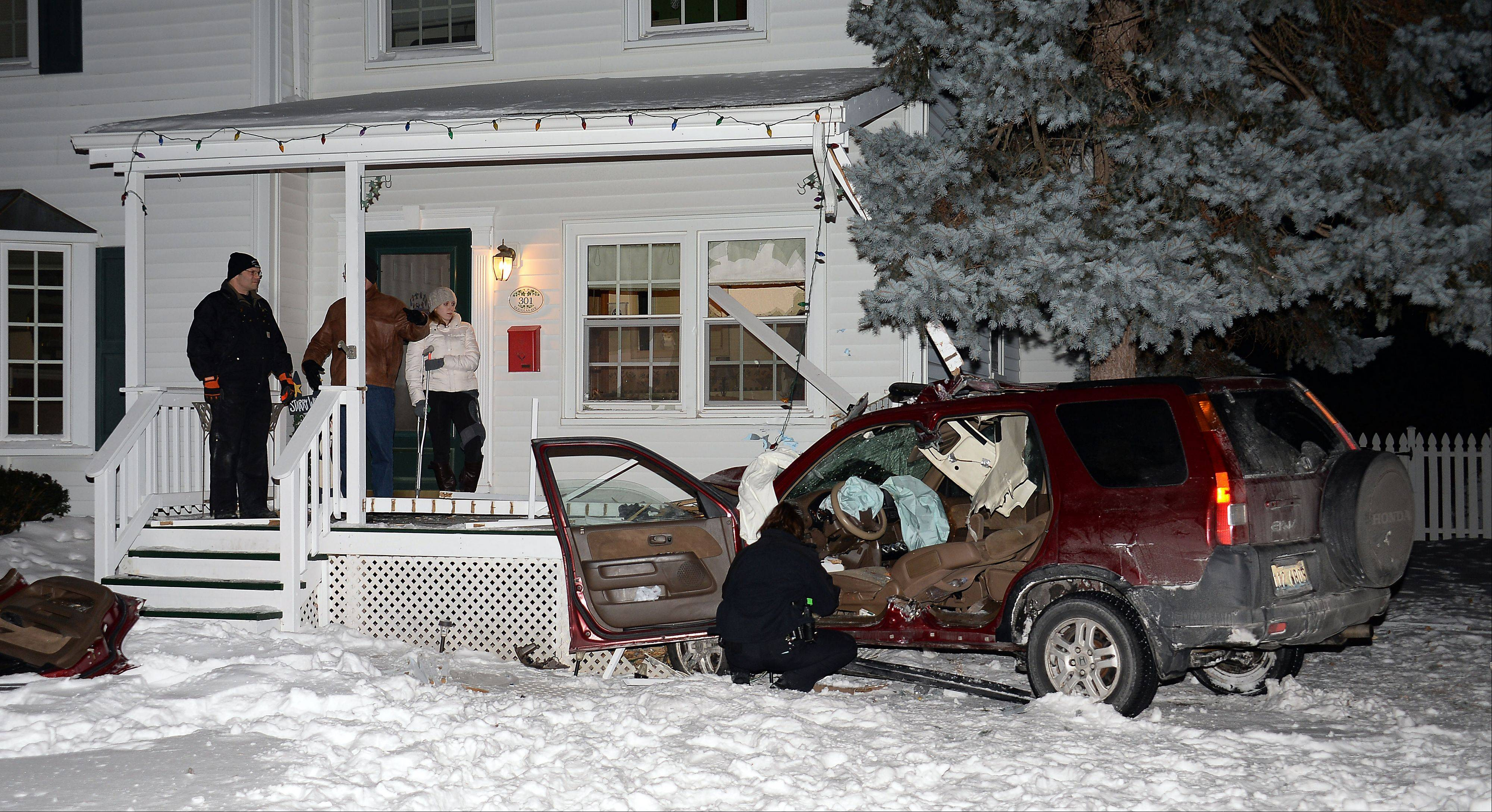 Arlington Heights police investigate the scene of a SUV crash into a house that occurred about 8 p.m. Thursday.