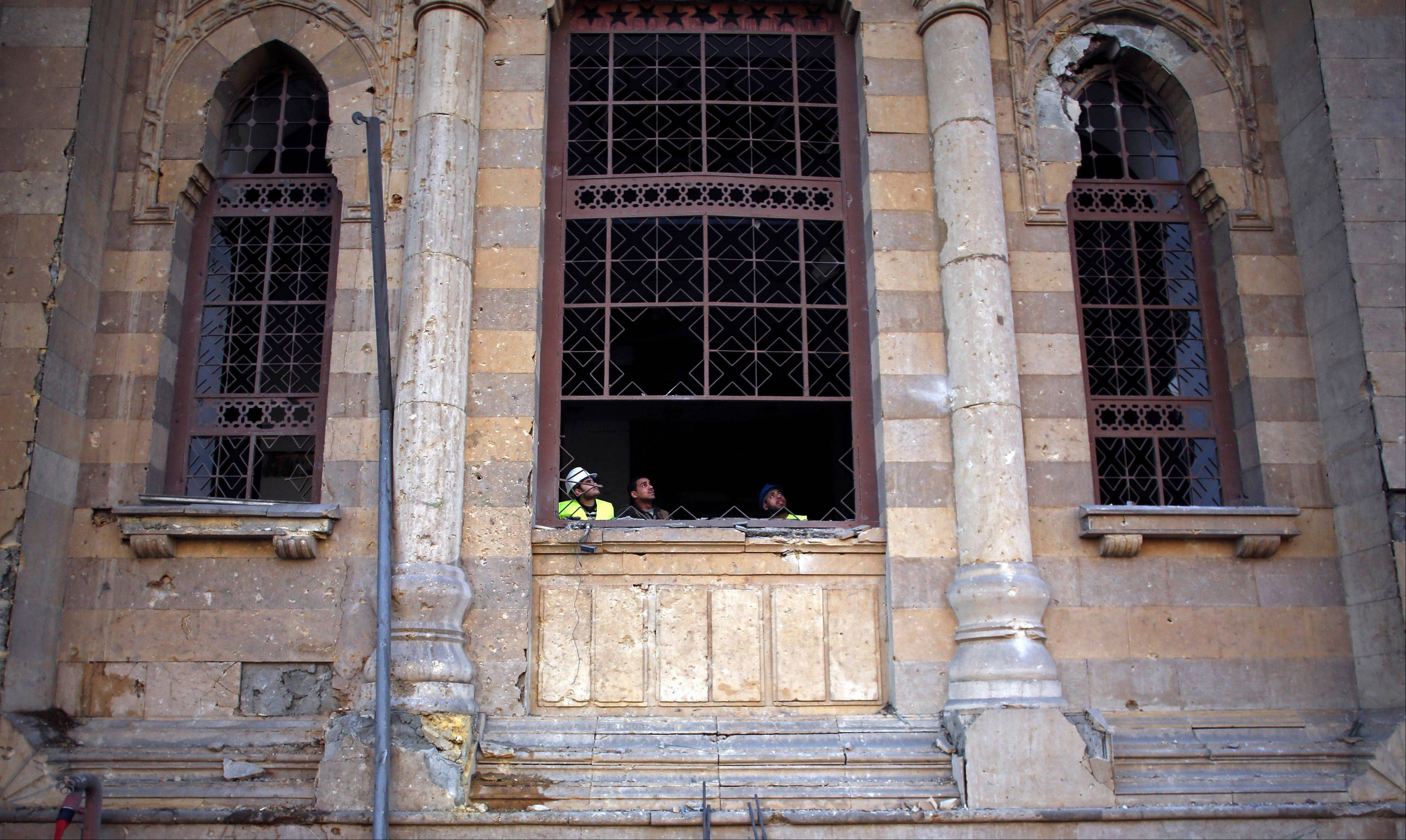 Egyptian workers peer Friday from the window of the damaged Museum of Islamic Art after an explosion at the Egyptian police headquarters in downtown Cairo.