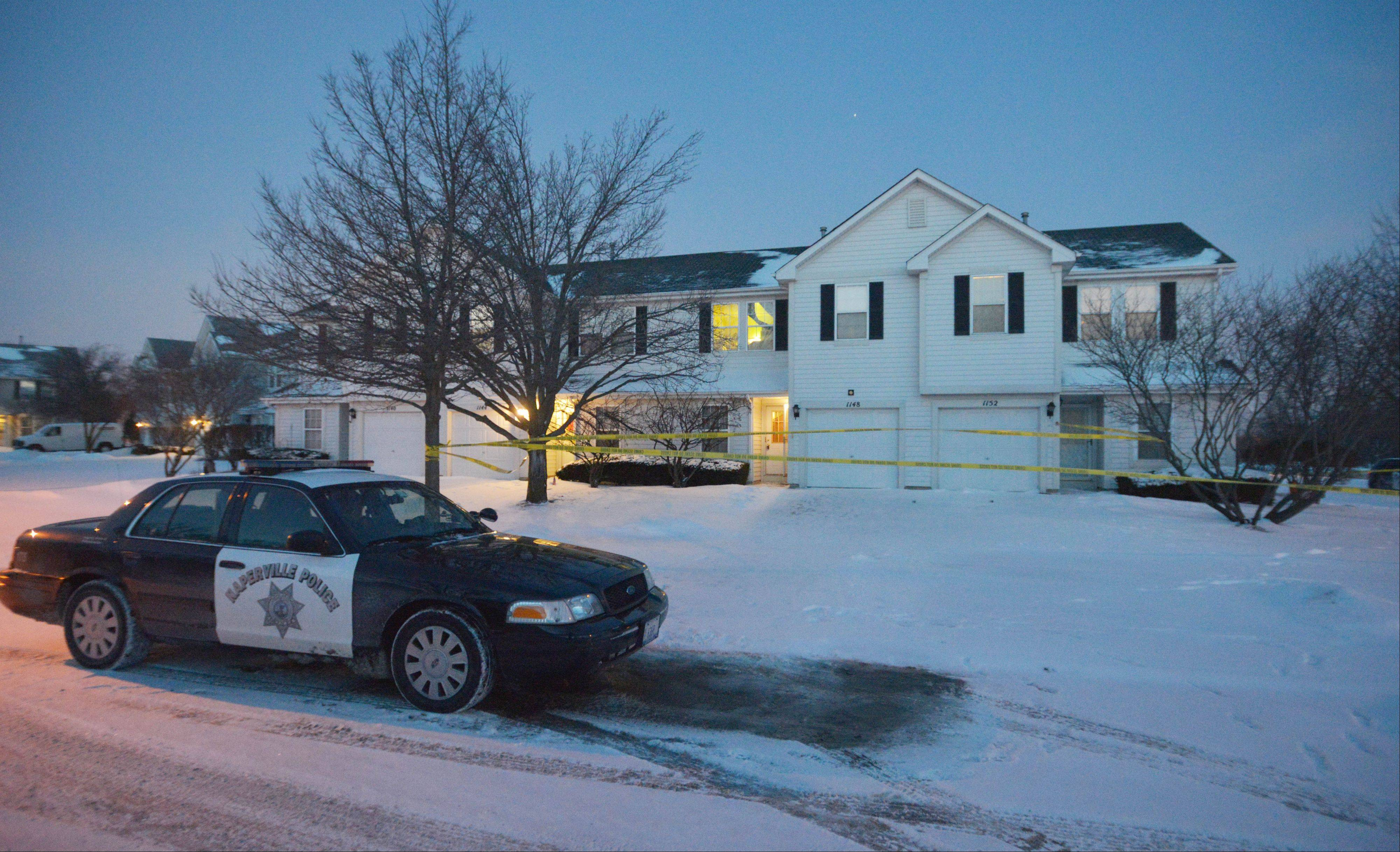 A Naperville police car idles in front of a townhouse on Vail Court in Naperville, where a man was found dead Wednesday morning.