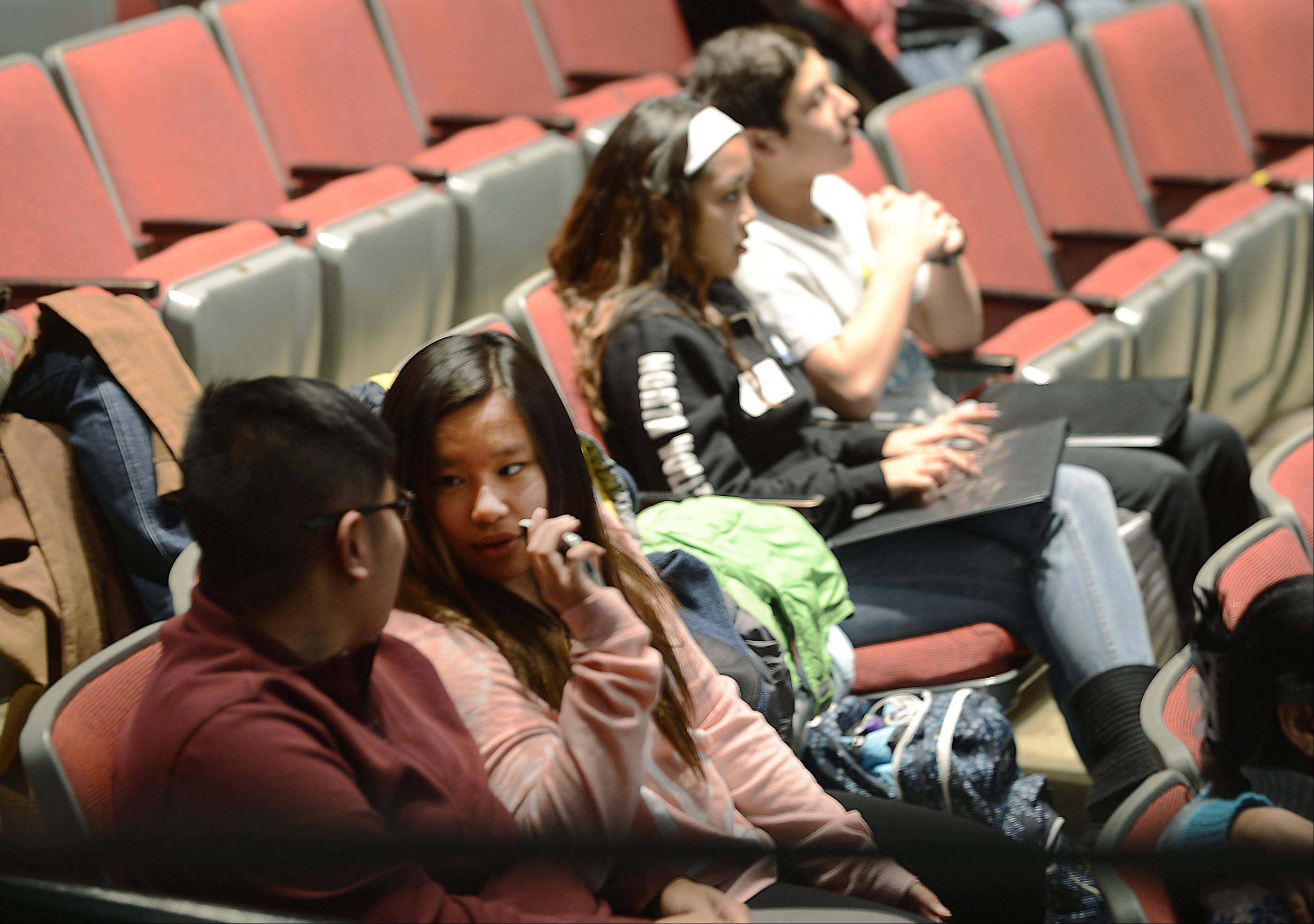 Danyelle Del Rosario, 15, talks quietly with her father Louie, of South Elgin, as her sister Ashriel, 12, sits with their cousin Jaden, 12, in the Blizzard Theater at Elgin Community College. They are three of six cousins playing in Saturday's American Grands XIX production.