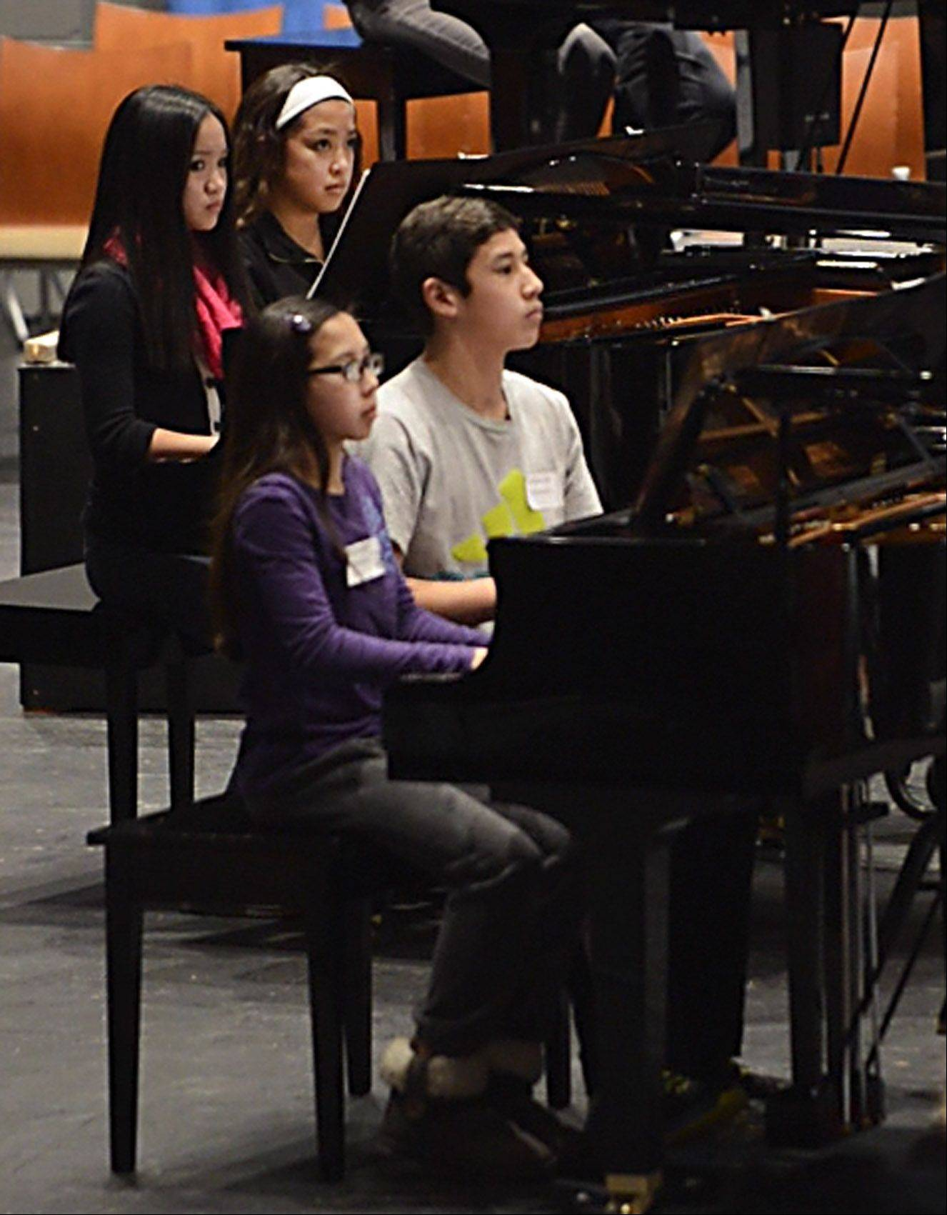 Siblings Izabella, 11, and Jaden Del Rosario, 12, play together as their cousin Ashriel Del Rosario, 12, rehearses on another grand piano for the American Grands XIX concerts at the Elgin Community College's Blizzard Theater.