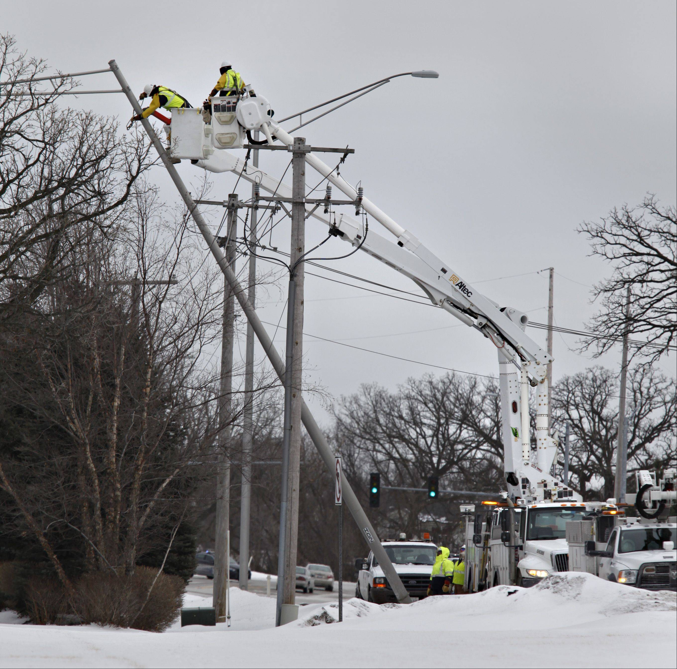 A ComEd crew works to secure an overhead streetlight along Huntley Road in Carpentersville that was likely blown over in Friday's high winds, landing on power lines below. More than 1,000 residents in Carpentersville, Algonquin and West Dundee were out of power for nearly 90 minutes.