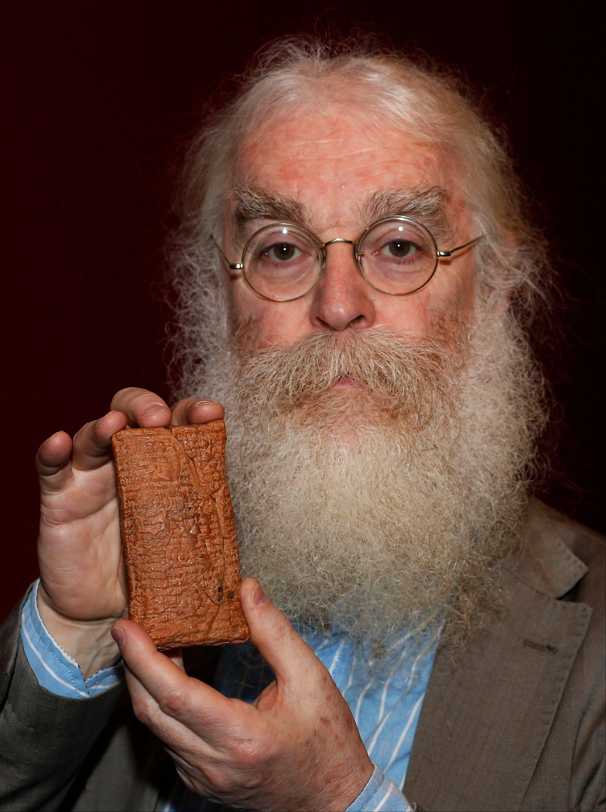 Irving Finkel, curator in charge of cuneiform clay tablets at the British Museum, poses Friday with the 4,000 year old clay tablet containing the story of the Ark and the flood during the launch of his book 'The Ark Before Noah' at the British Museum in London.