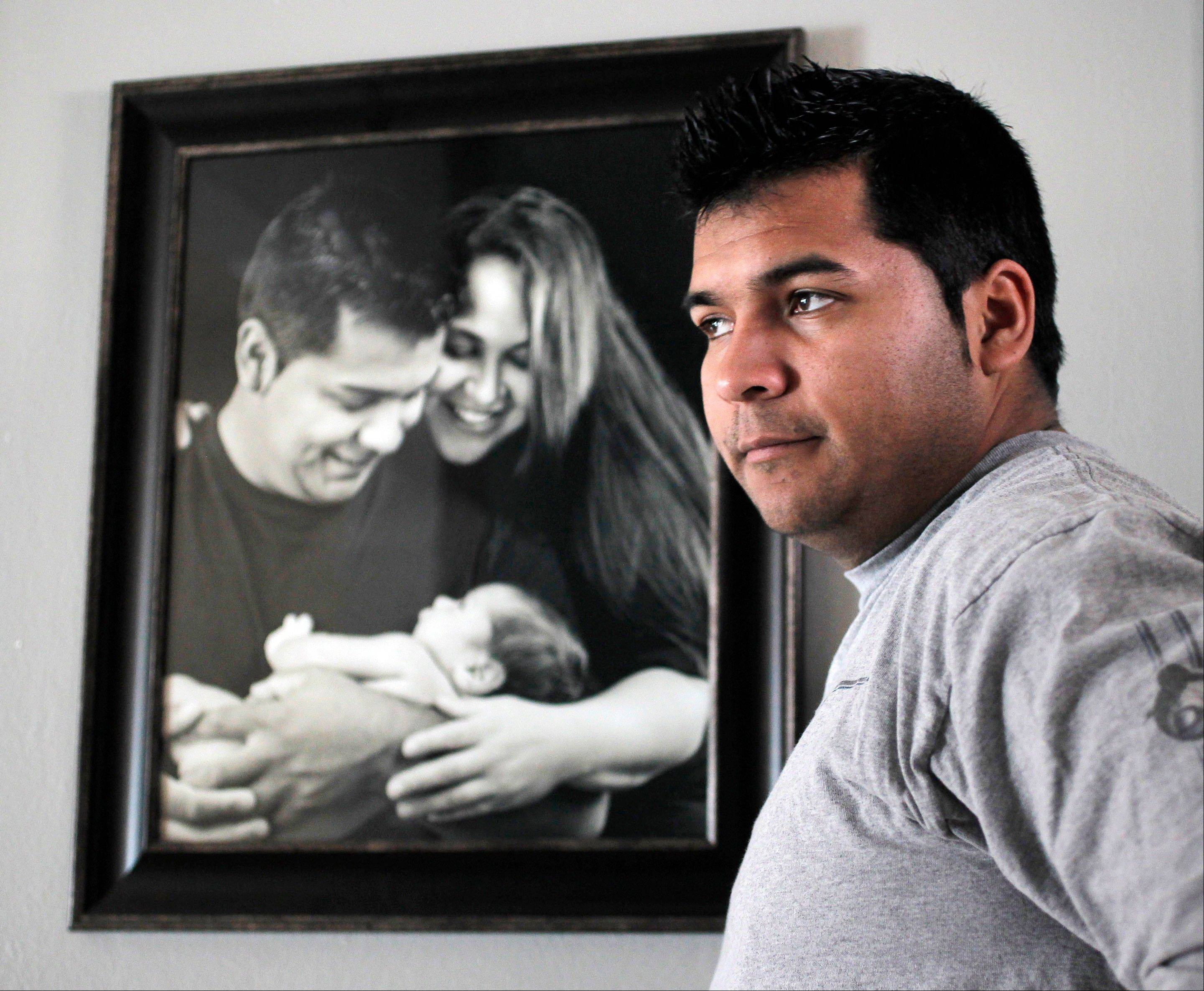 Erick Munoz stands with a photograph of himself, left, with wife Marlise and their son Mateo.