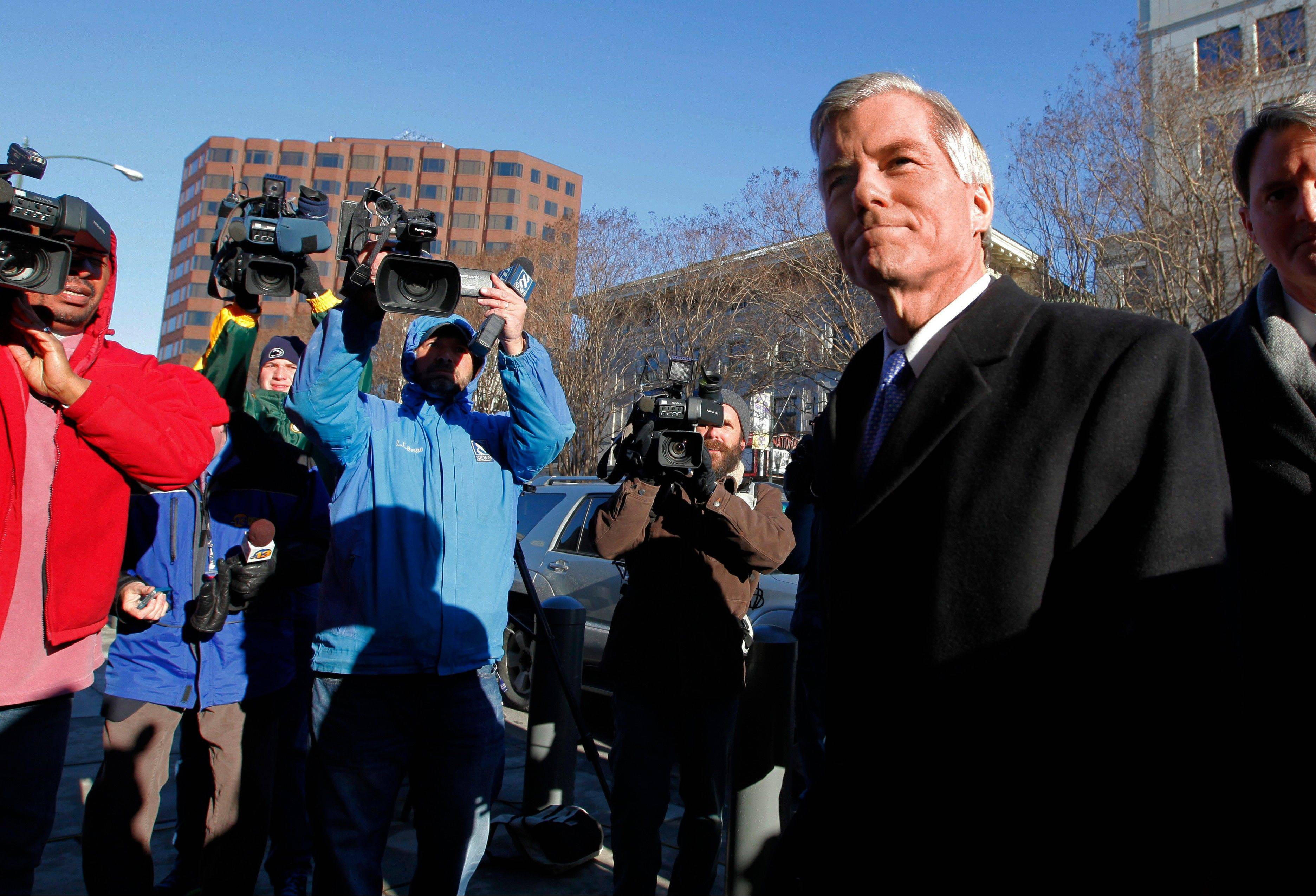 Former Va. Governor Bob McDonnell, right, surrounded by news cameras, enters U.S. District Court in Richmond, Va. for his and his wife Maureen's bond hearing and arraignment on Friday, Jan. 24, 2014 on federal corruption charges. The McDonnells, flanked by their children, did not comment as they entered the courthouse.
