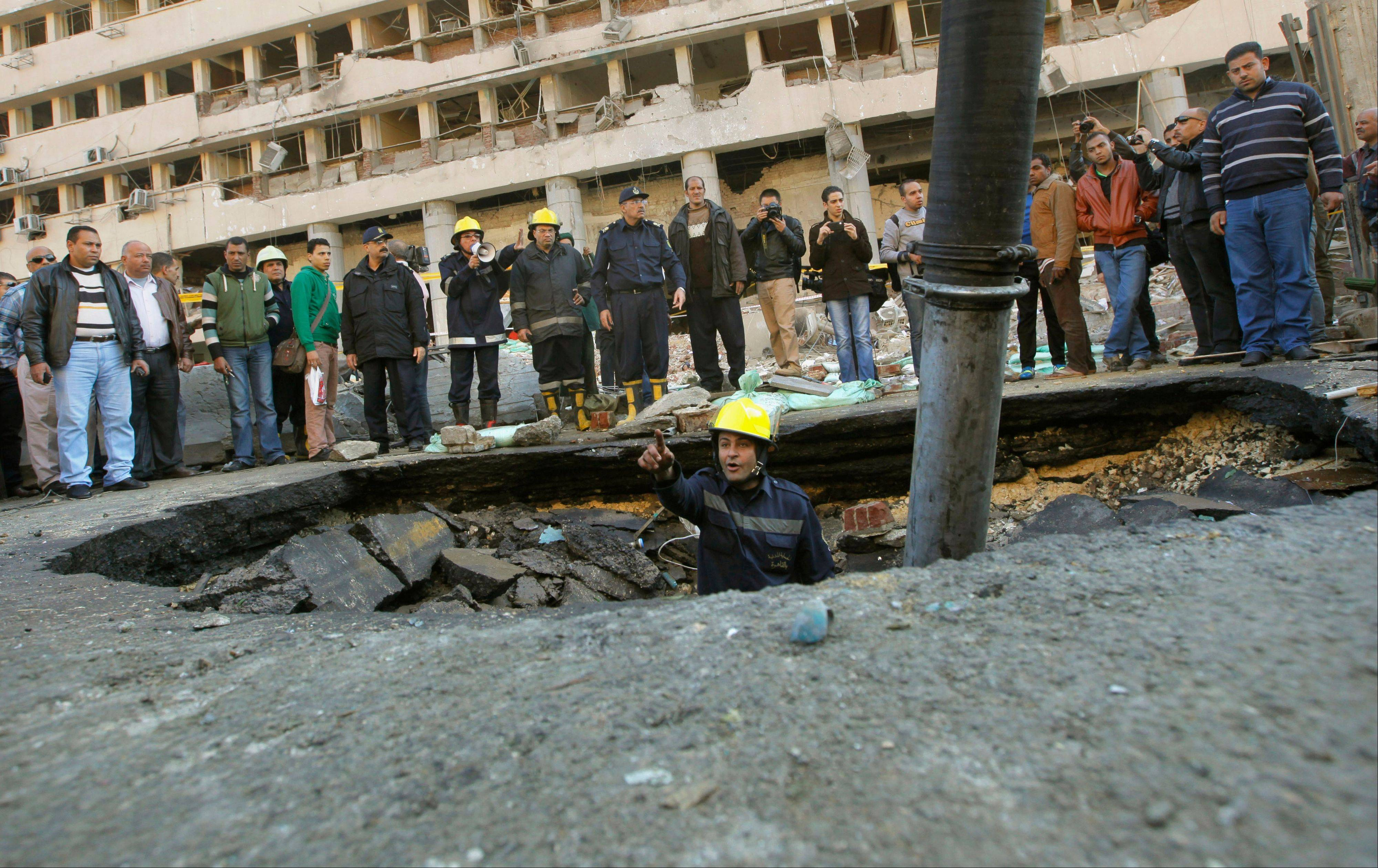 An Egyptian firefighter checks a crater made by a blast at the Egyptian police headquarters in downtown Cairo, Egypt, Friday, Jan. 24, 2014. Three bombings hit high-profile areas around Cairo on Friday, including a suicide car bomber who struck the city's police headquarters.