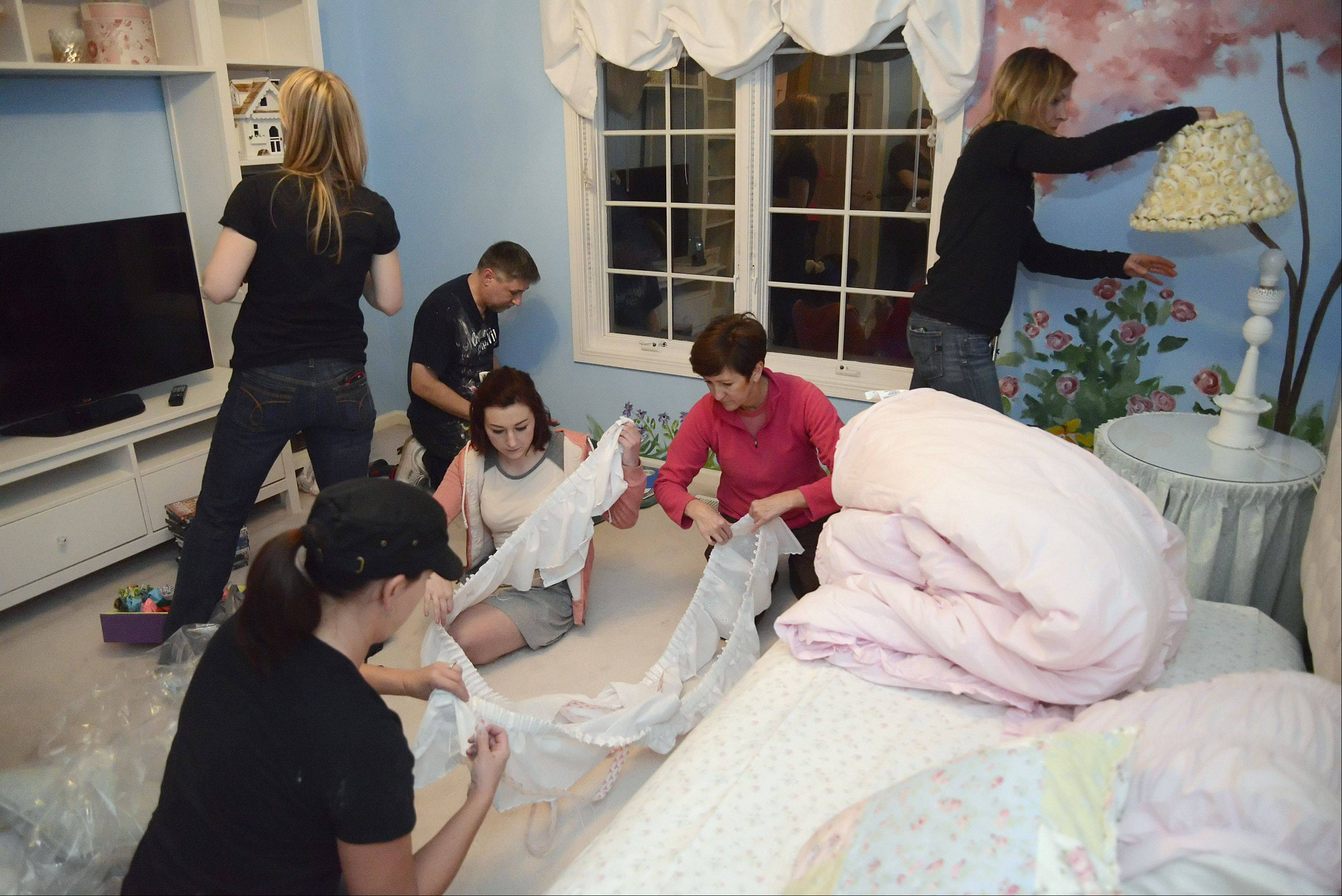 The Special Spaces Chicagoland team and volunteers pull together the new bedroom for Catharine Steiner of St. Charles before her arrival Thursday. From left to right, Lori McSpadden, seated, Andrea Schwemin, standing, Genevieve Cipriano and her mother Beth, center, Ken Markiewicz and Kelly Knox. Genevieve, 18, is a cancer survivor and was the recipient of a room makeover in November; she wanted to pay it forward in helping another child.