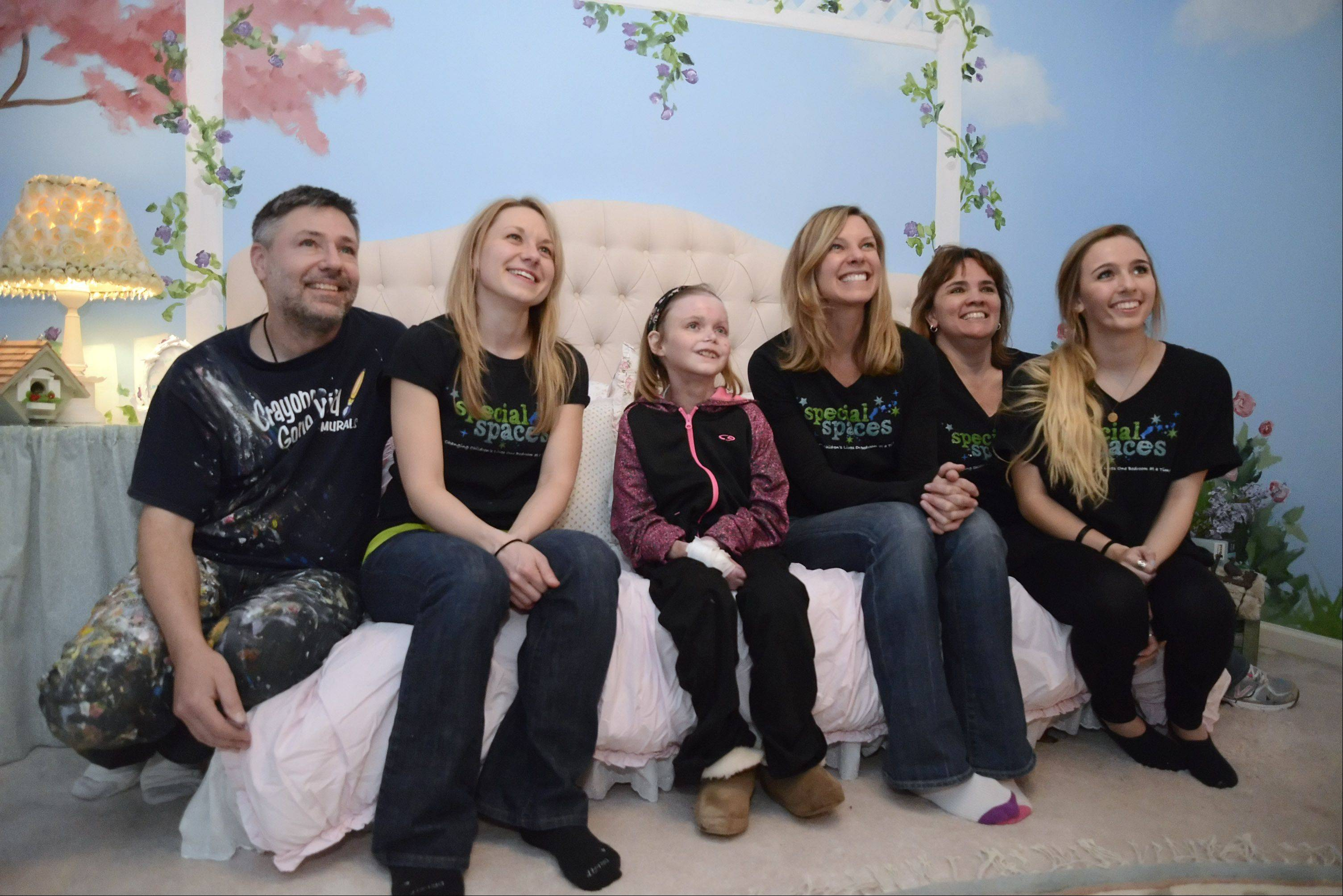 Catharine Steiner, 16, of St. Charles, center, sits with the Special Spaces Chicagoland team for photos after they made over her bedroom in one day. From left to right, Ken Markiewicz, Andrea Schwemin, who designed the room, Catharine, Kelly Knox, Judy Markiewicz and daughter Jamie Markiewicz. Lori McSpadden, not pictured, was also on the team.