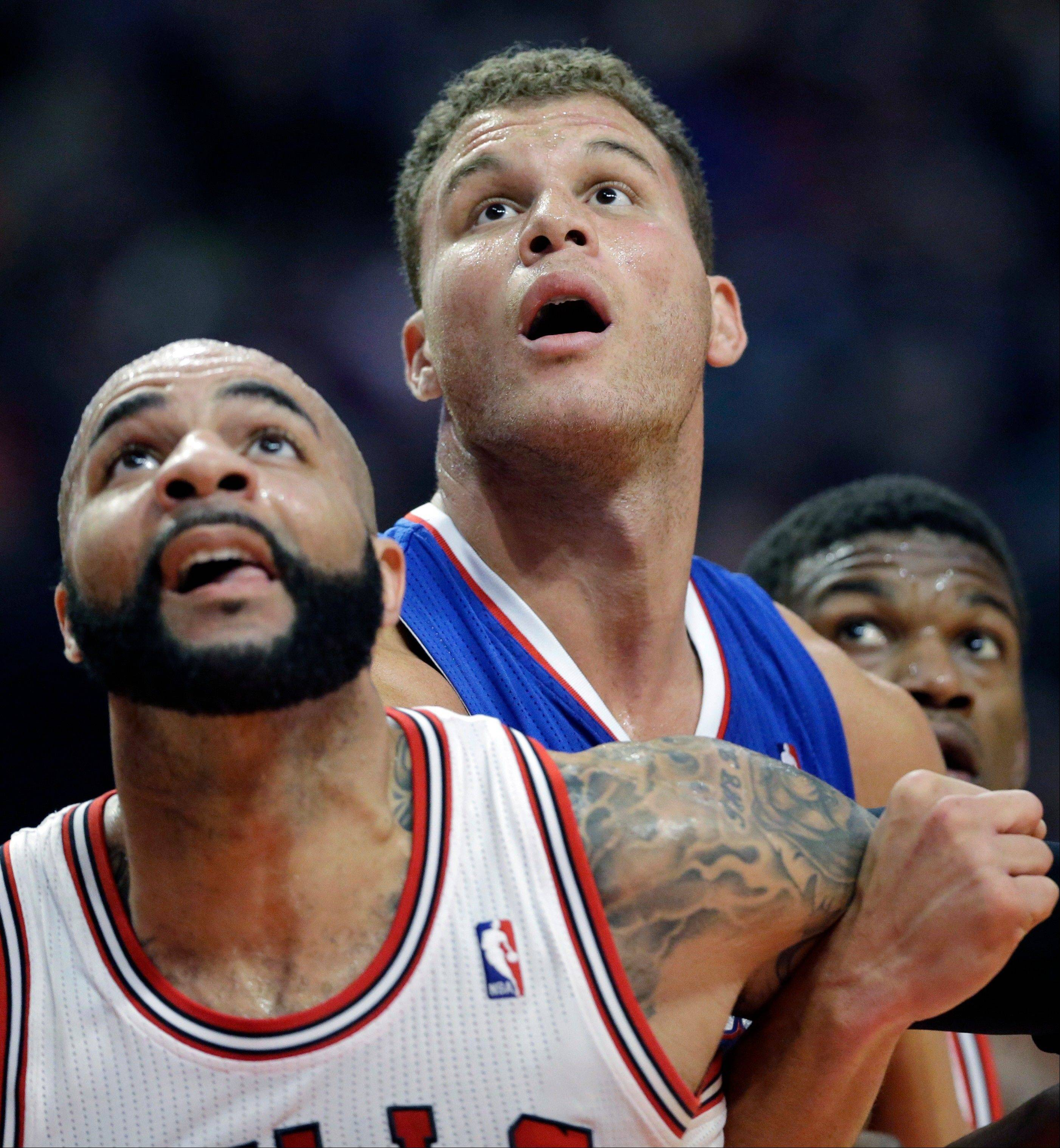 Los Angeles Clippers forward Blake Griffin, center, battles for a rebound against Chicago Bulls forward Carlos Boozer, left, and guard Jimmy Butler during the first half of an NBA basketball game in Chicago on Friday, Jan. 24, 2014.