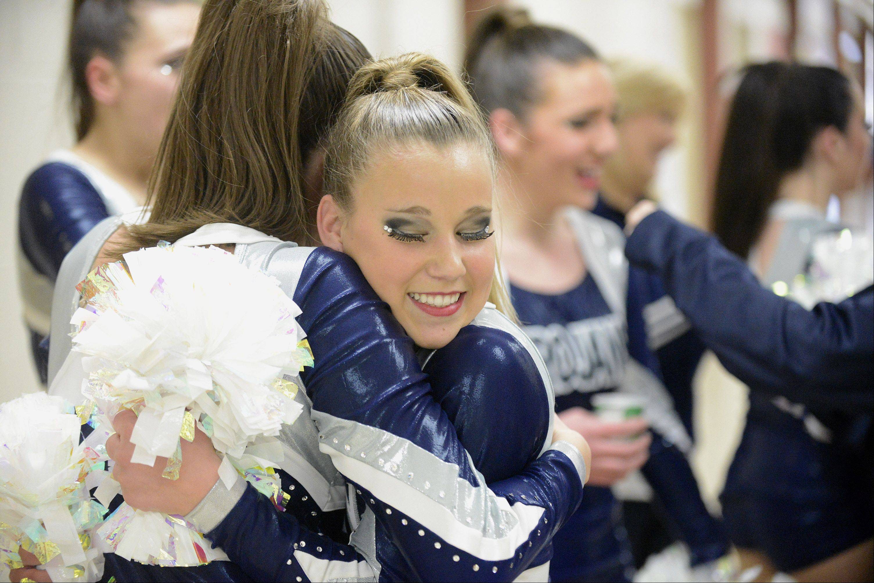 Cary Grove's Megan Emma, 15, facing, hugs teammate Anna Baran, 17, after their performance at the IHSA 2A competitive dance sectionals at Huntley High School on Saturday, January 25. The team took third place and is heading to the state competition.