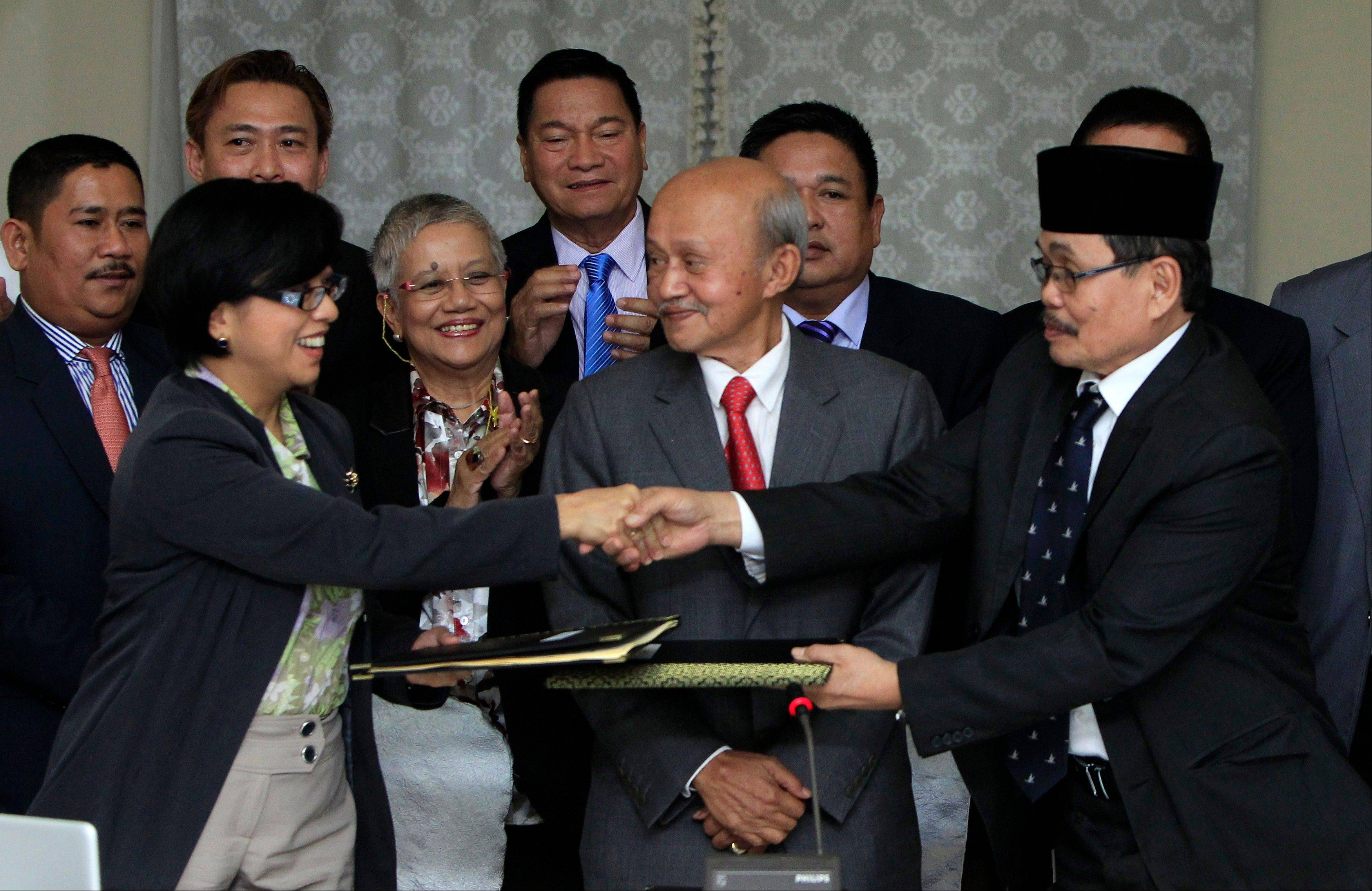Miriam Coronel-Ferrer, front left, chairperson of Philippine Government Peace Panel, and Mohagher Iqbal, front right, chief negotiator for the Moro National Liberation Front, exchange signed documents Saturday as Malaysian facilitator Abdul Ghafar Tengku Mohamed, front center, witnesses after the 43rd GPH-MILF Exploratory Talks in Kuala Lumpur, Malaysia.