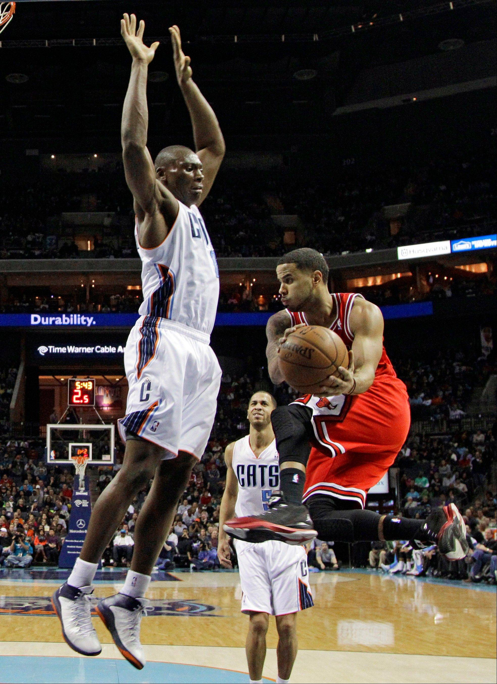 The Bulls� D.J. Augustin, right, looks to pass around Charlotte Bobcats� Bismack Biyombo, left, during Saturday night�s game in Charlotte, N.C. The Bulls beat the Bobcats 89-87.