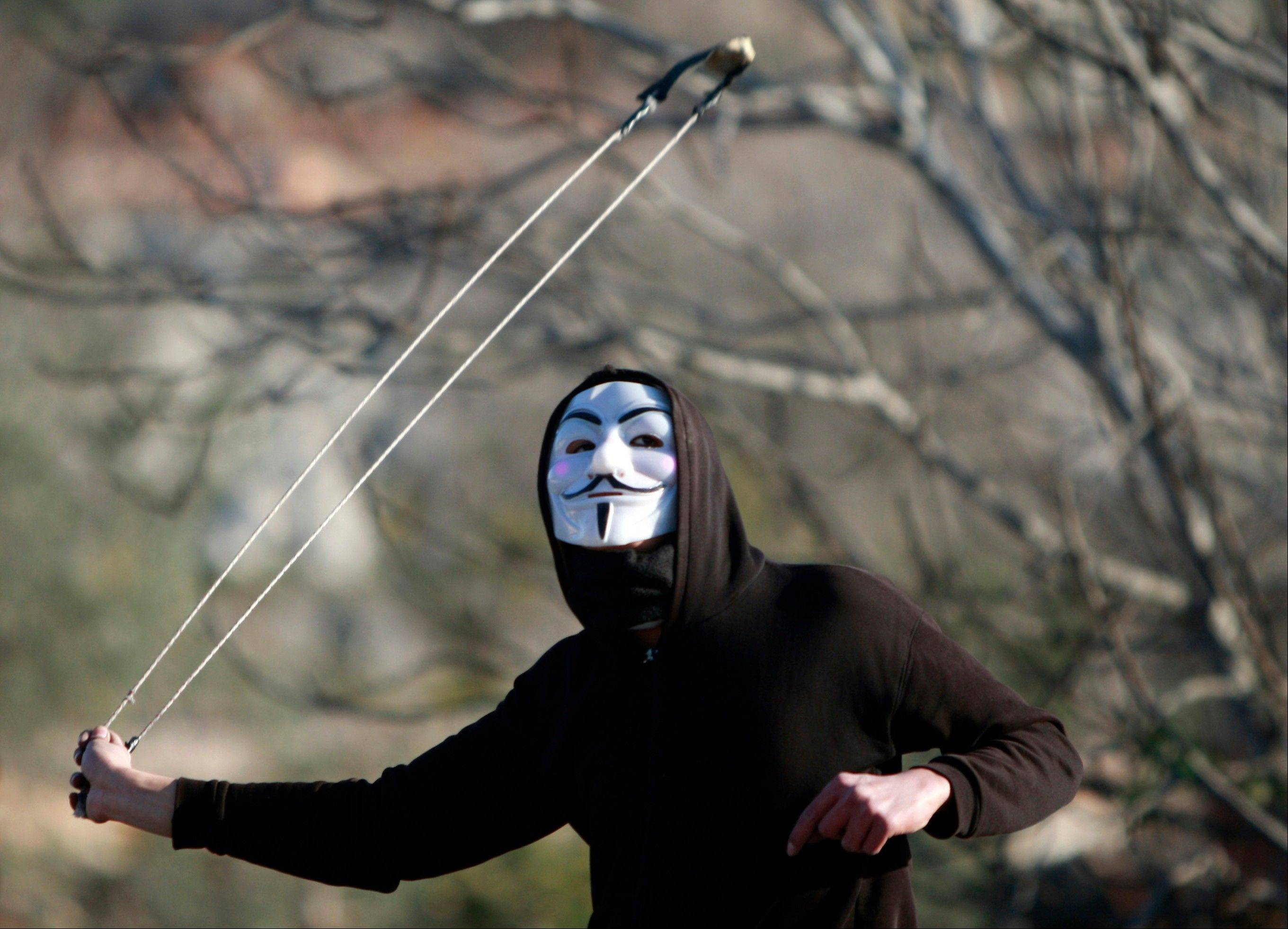 A Palestinian uses a slingshot Friday to hurl stones at Israeli soldiers during a weekly protest in the village of Silwad, near the West Bank city of Ramallah.